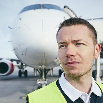 Close up image of a Caucasian airport employee outside close to the front of a plane which is close behind