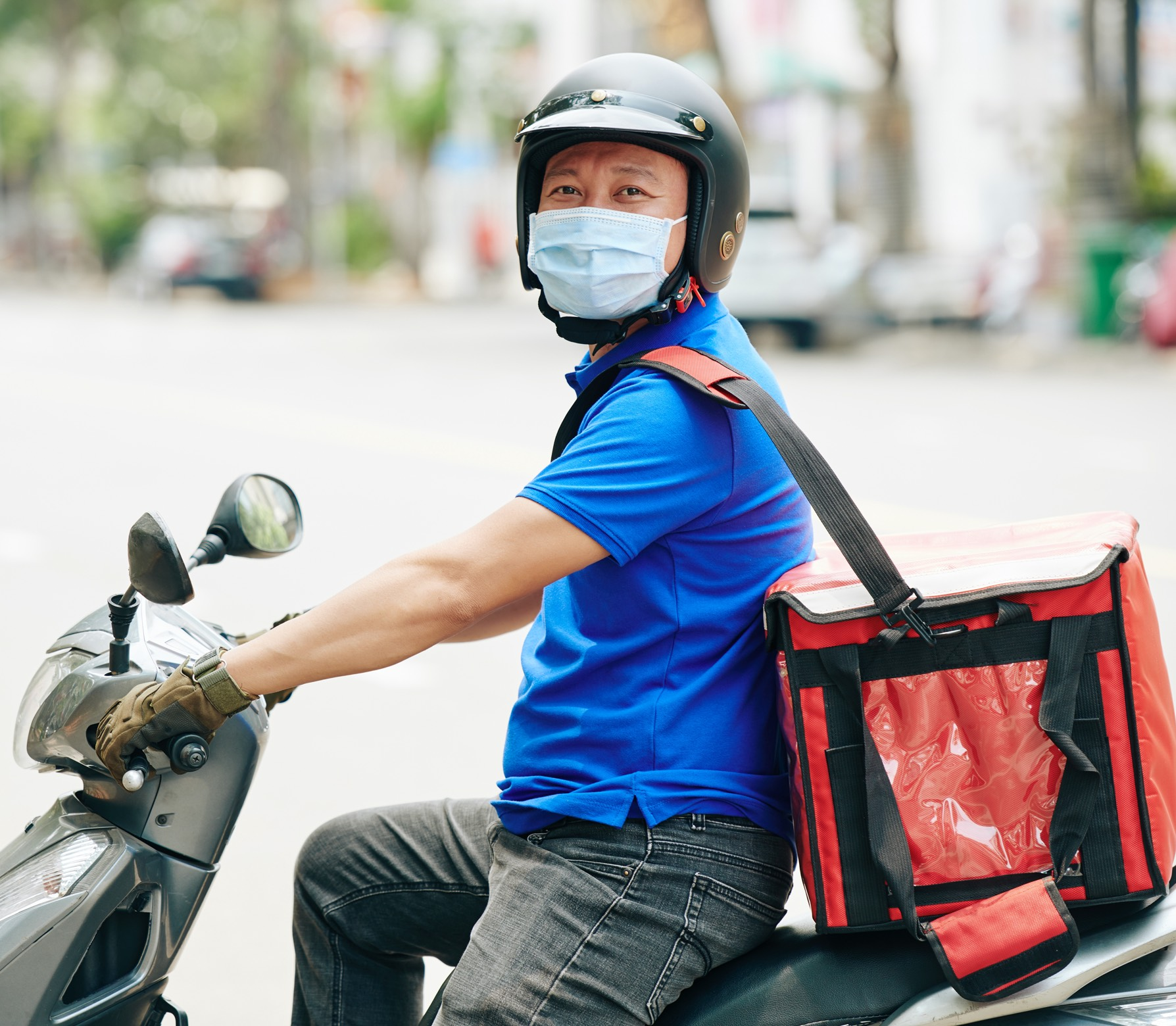 Image of a male delivery driver on a moped smiling at the camera whilst wearing facial PPE and a food delivery backpack on his back