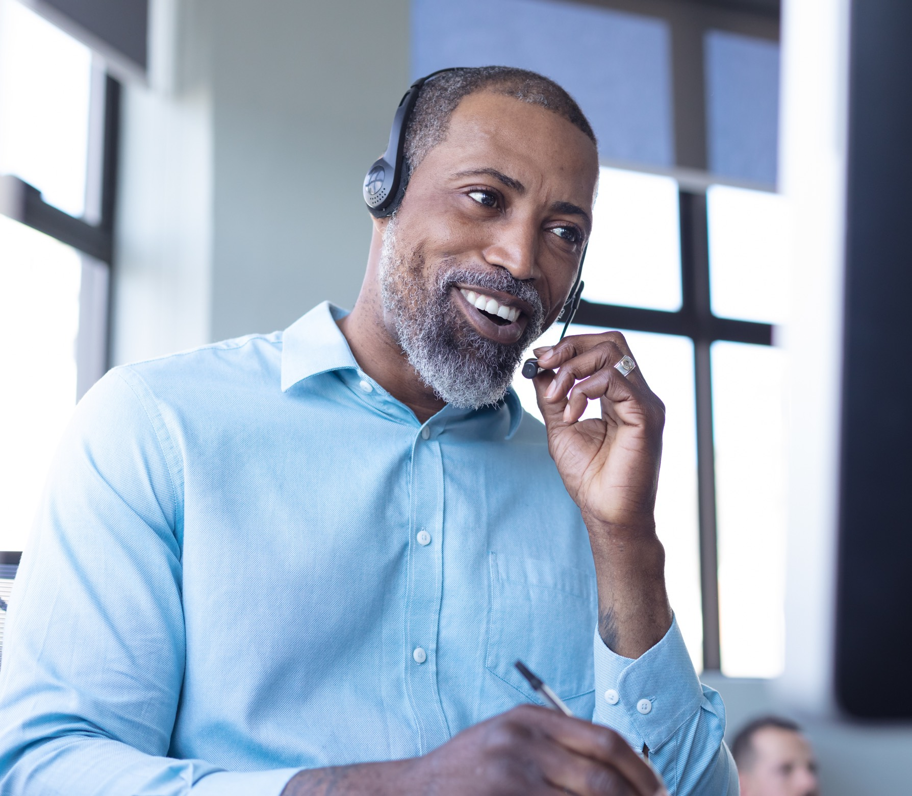 Image of a male call center employee smiling whilst taking a call with a customer