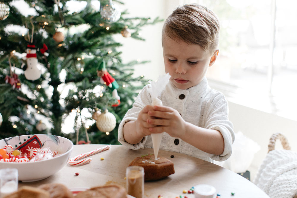 A young boy decorating christmas cookies