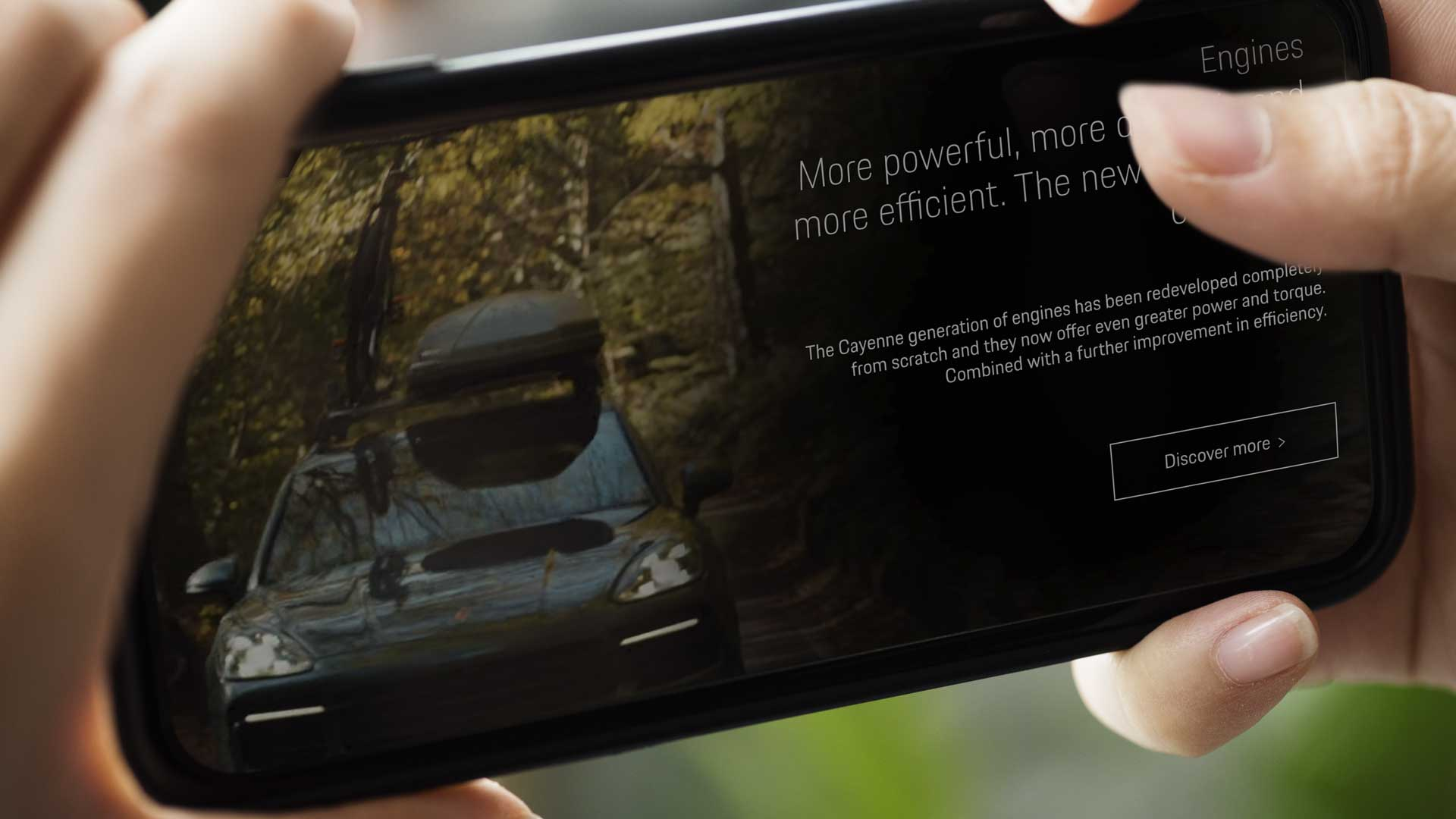 A mobile phone with an interactive video playing on the screen. It is an interactive video for the automotive brand Porsche. The overlay on screen calls out features of the car.
