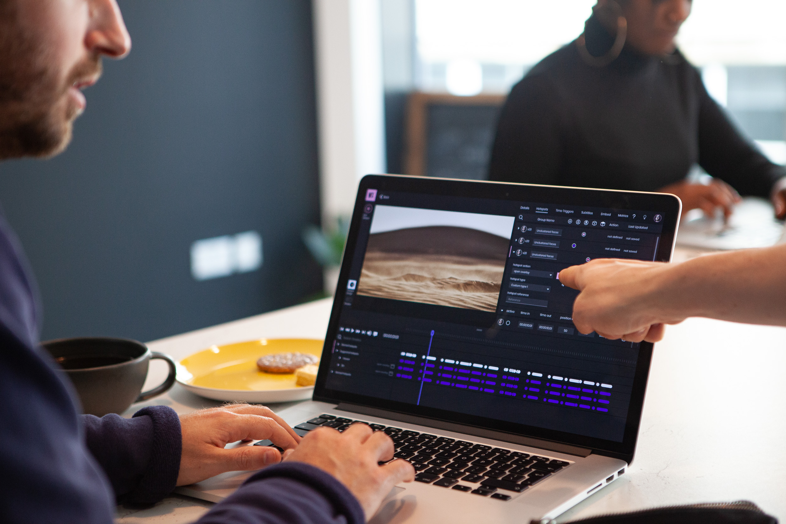 A man sits at a laptop creating an interactive video using WIREWAX Studio. Someone is pointing to a detail on the screen off frame.