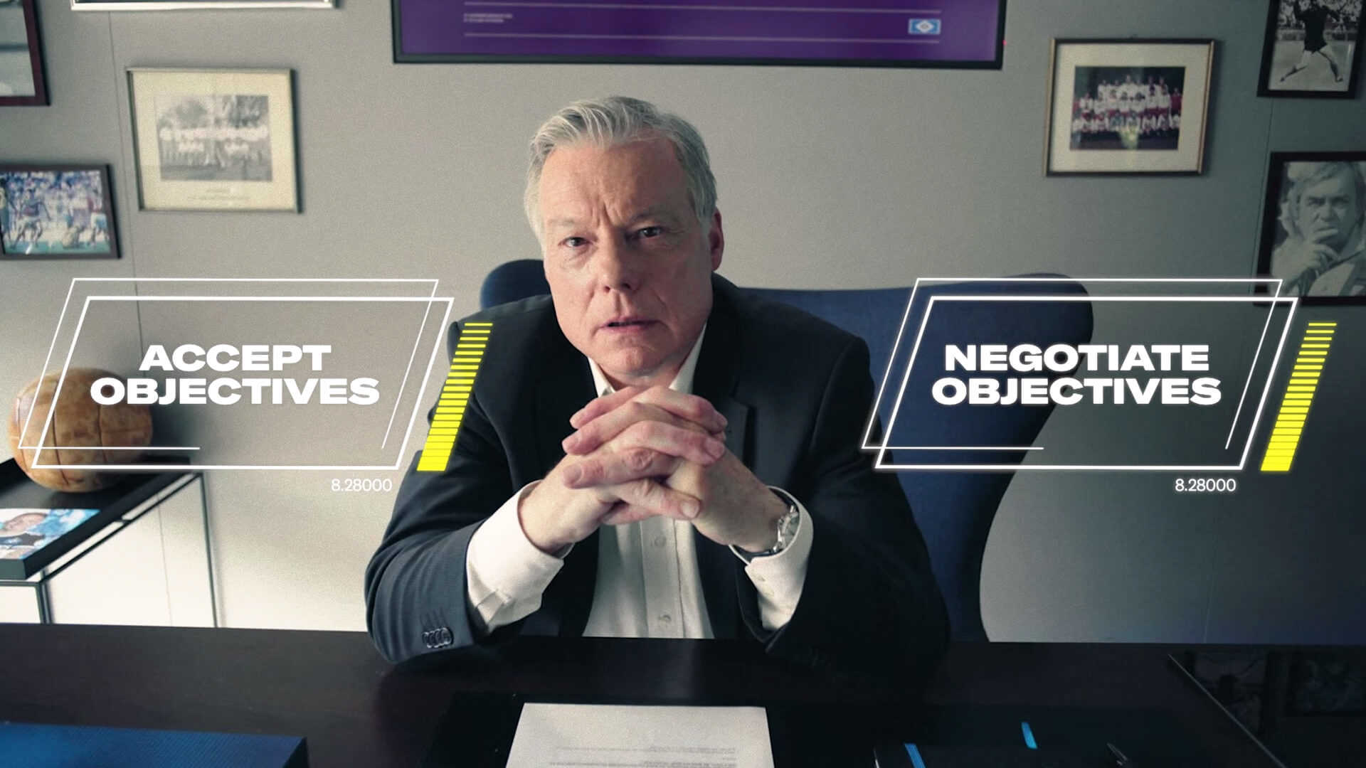 A still from a interactive video for Sega's Football Manager. A man sits behind the desk looking into the camera. To the left and right of him are two interactive hotspots acting as decisions to be made in the interactive video.