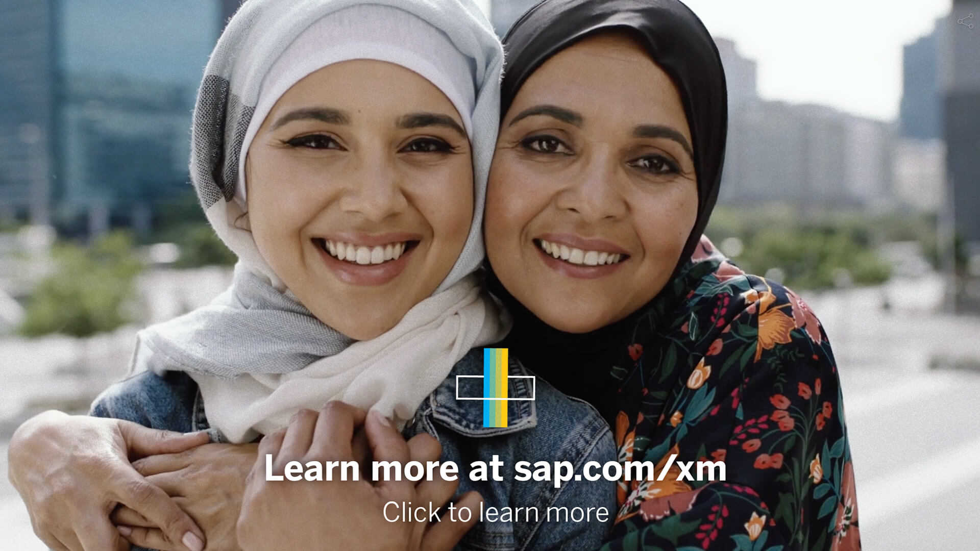 A still from an interactive video for SAP. Two women are hugging and looking into the camera. Below them is a clickable hotspot.