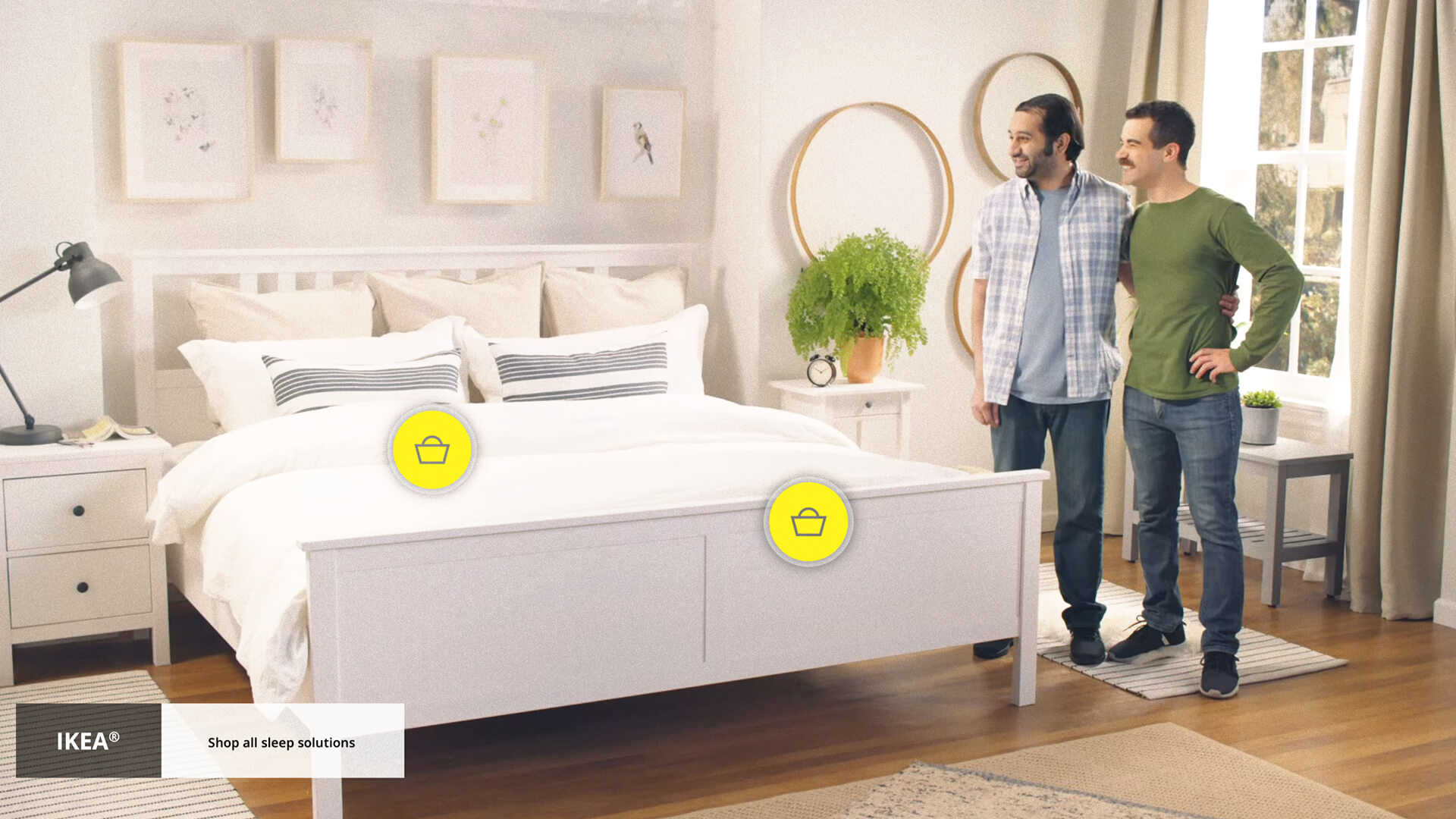 A still from a shoppable video from the furniture brand Ikea. Two males stand next to a bed. On the bed are two clickable hotspots with shopping bag icons on it.