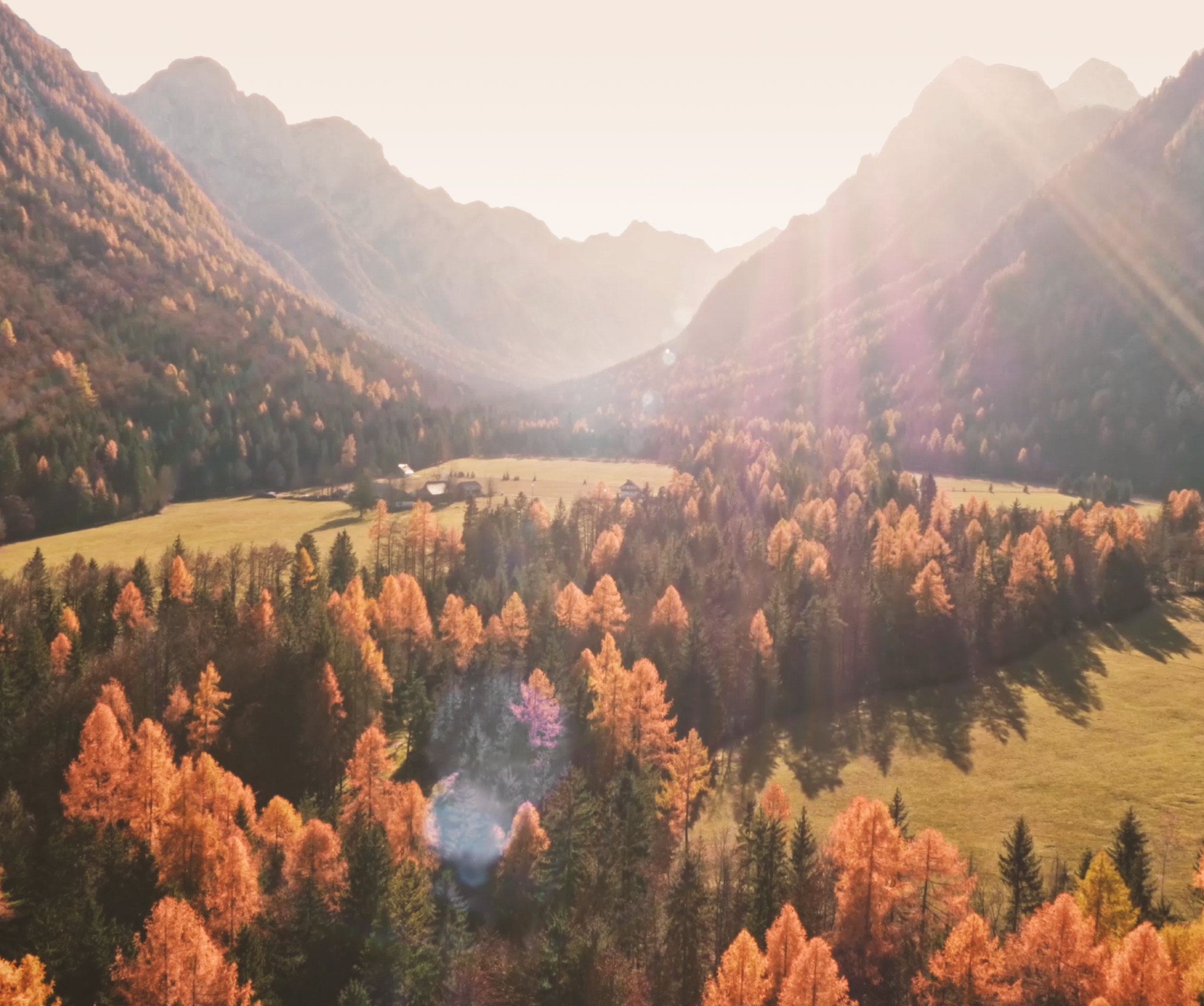 Still from the video depicting a full view of a valley, with trees, grass fields and mountains.