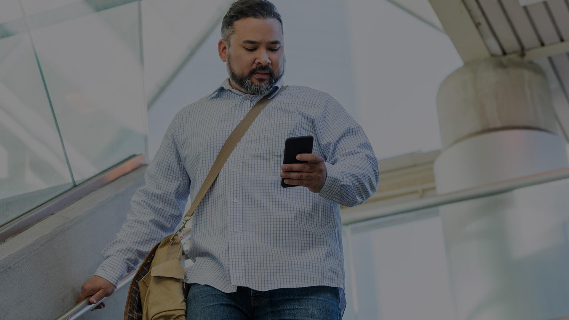 Man on phone pointing at laptop.