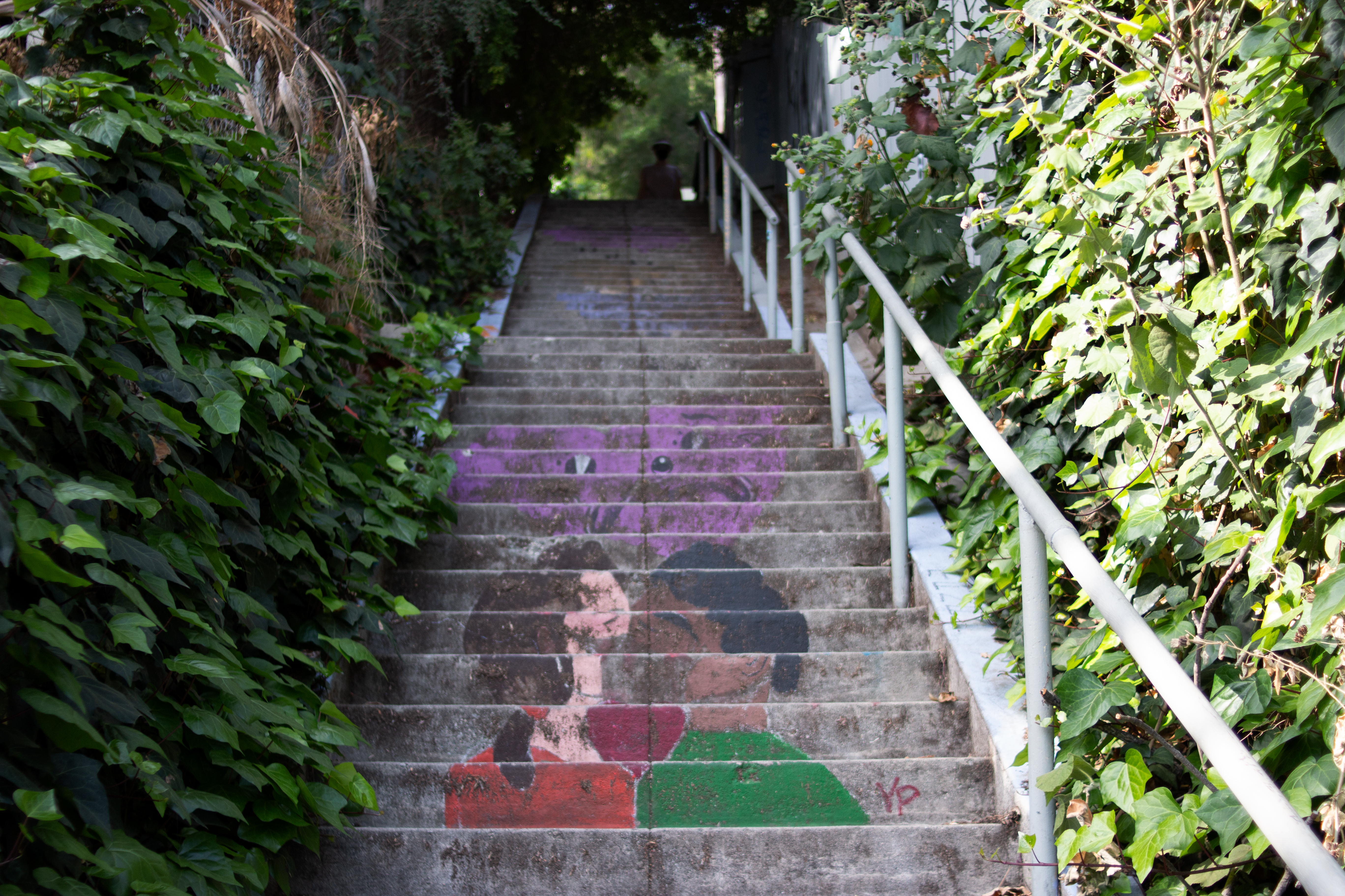 Faded painted staircase depicts couple kissing and crying hearts.