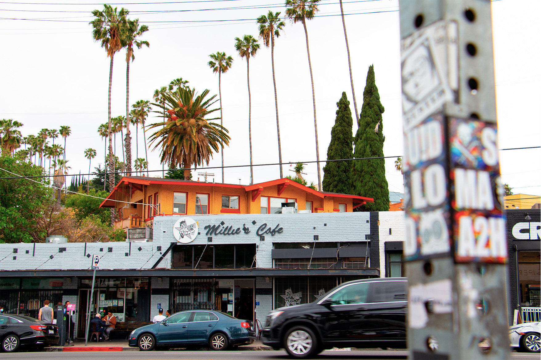 Street view of Millie's Cafe, a grey brick restaurant backing a palm tree–lined hillside.
