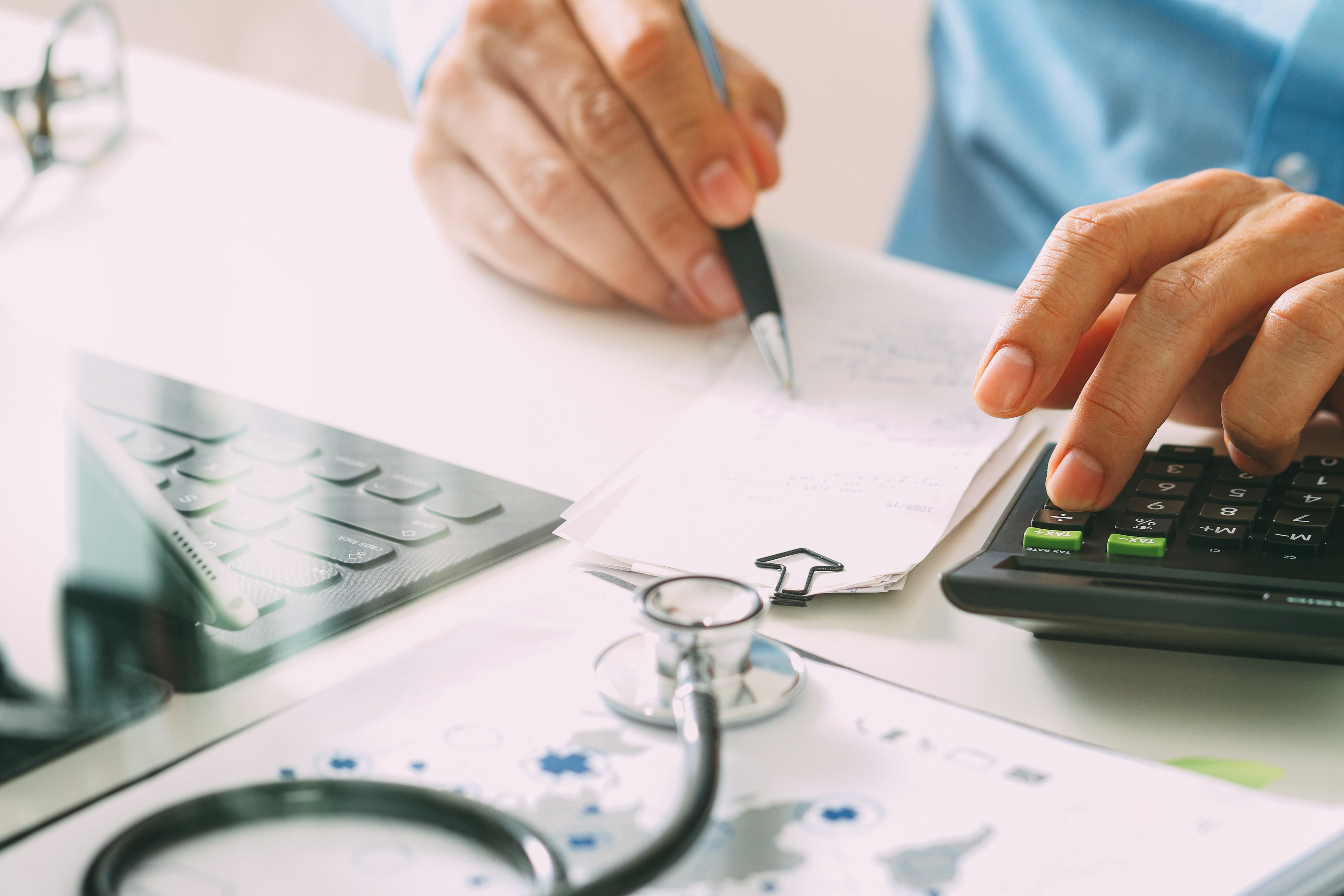 Healthcare costs and fees concept.Hand of smart doctor used a calculator for medical costs in modern hospital
