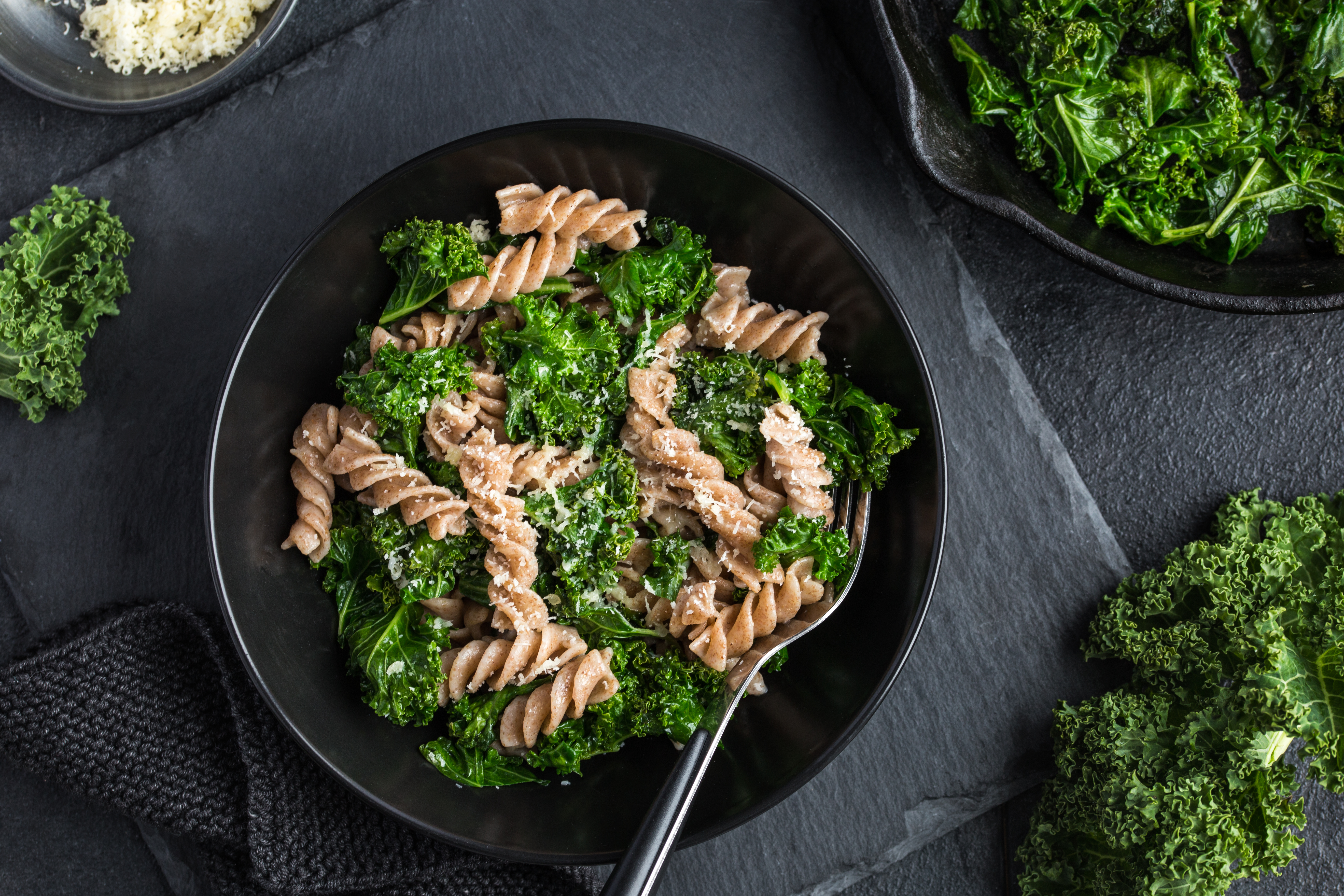 Whole grain pasta with kale in black bowl on dark background, top view