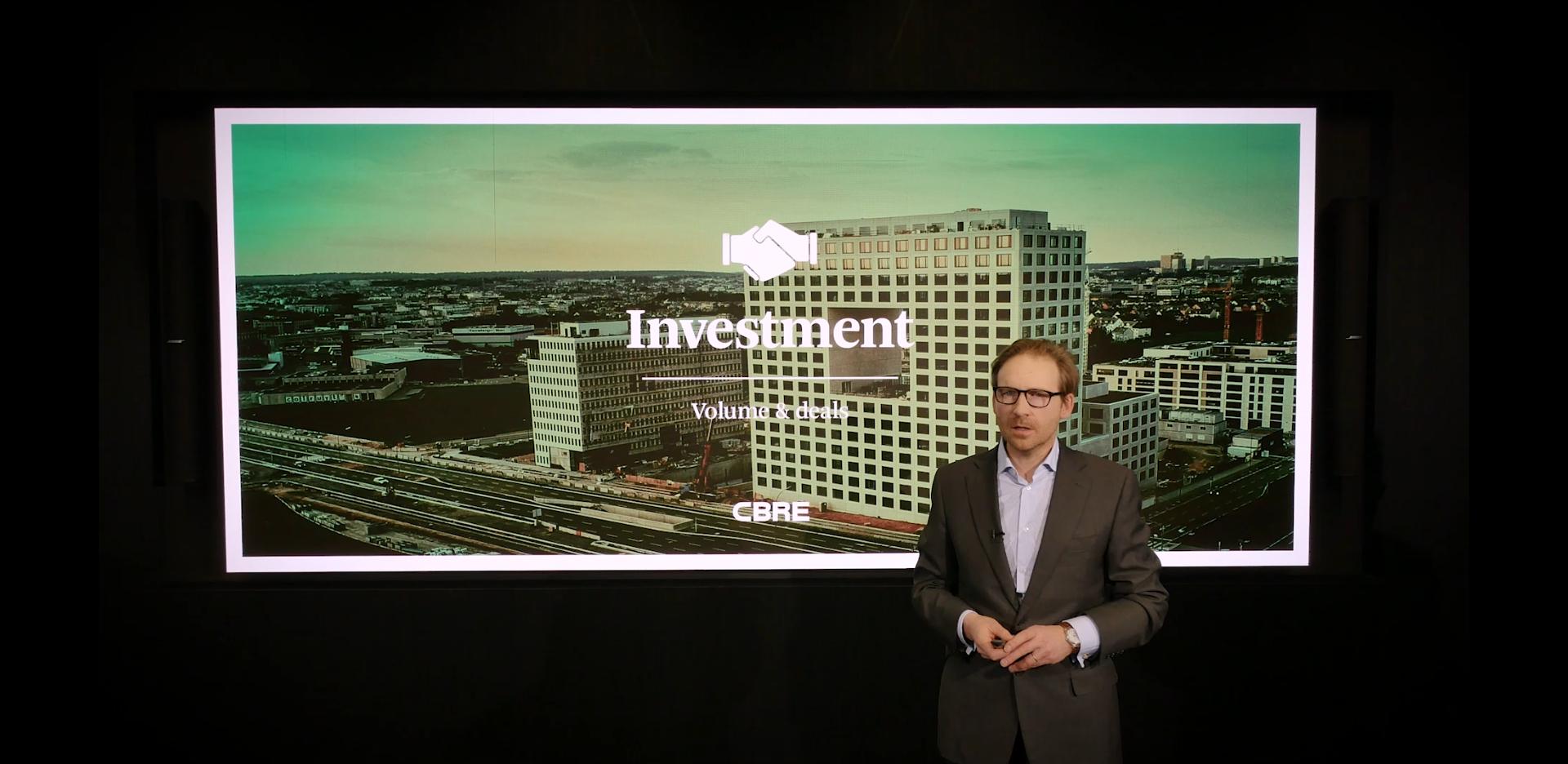 Jérôme Coppée parle du marché luxembourgeois de l'immobilier d'investissement devant sa présentation affichée sur un grand écran LED lors du webinaire Outlook 2021.