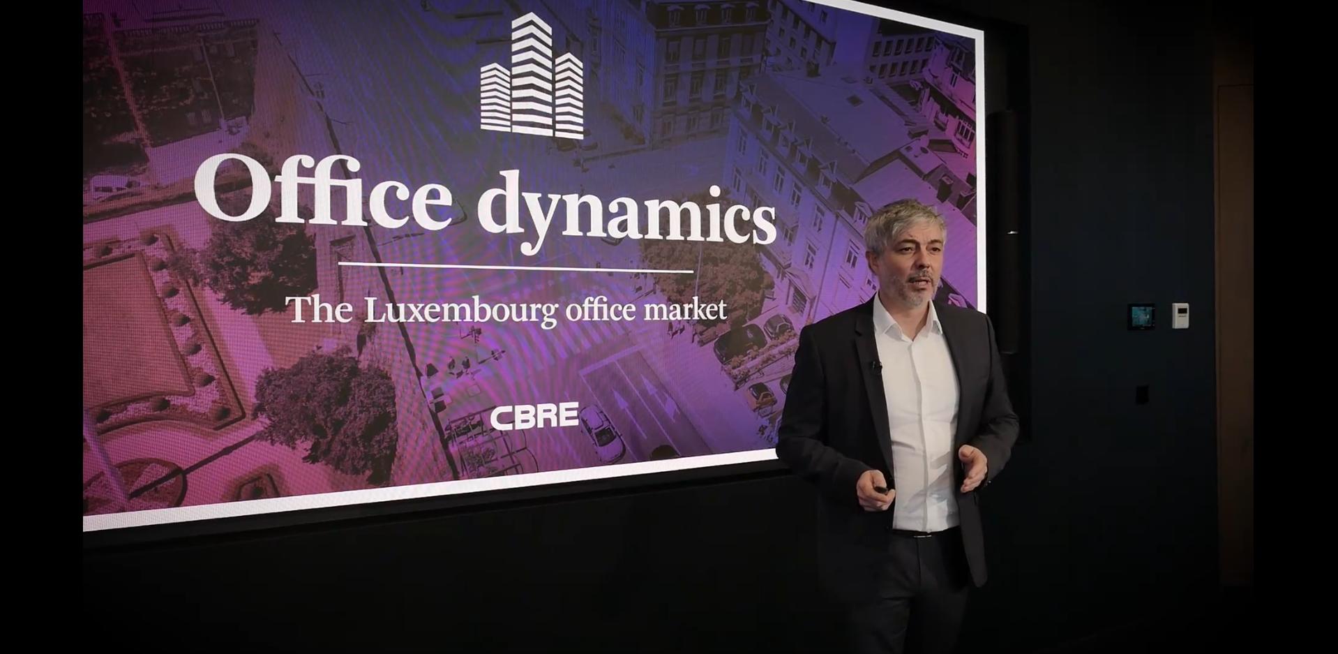 William Moulin parle du marché luxembourgeois des bureaux devant sa présentation affichée sur un grand écran LED lors du webinaire Outlook 2021.