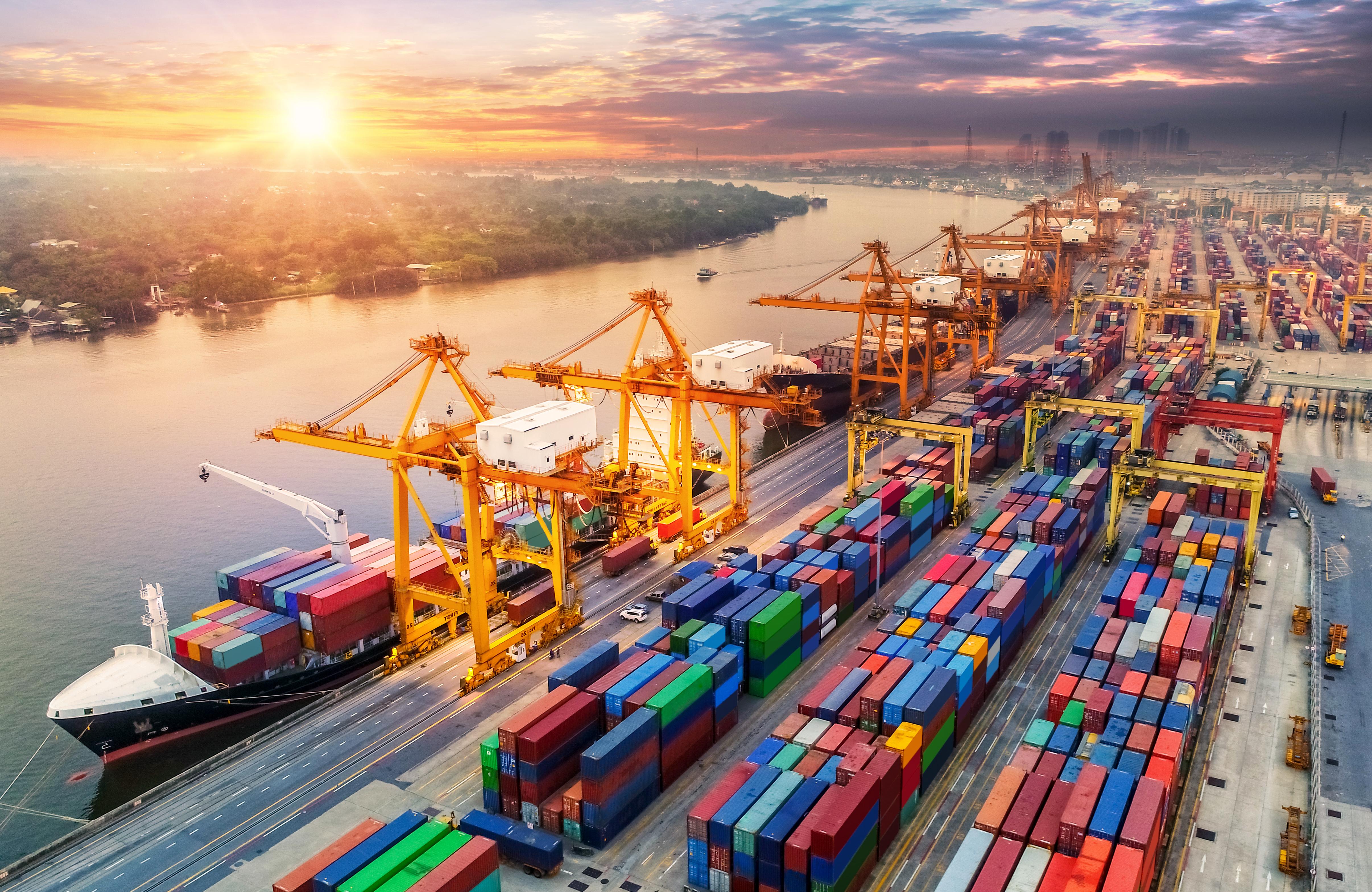 集装箱货船和货运飞机的物流和运输与工作的起重机桥梁在日出的造船厂,物流进口出口和运输产业背景