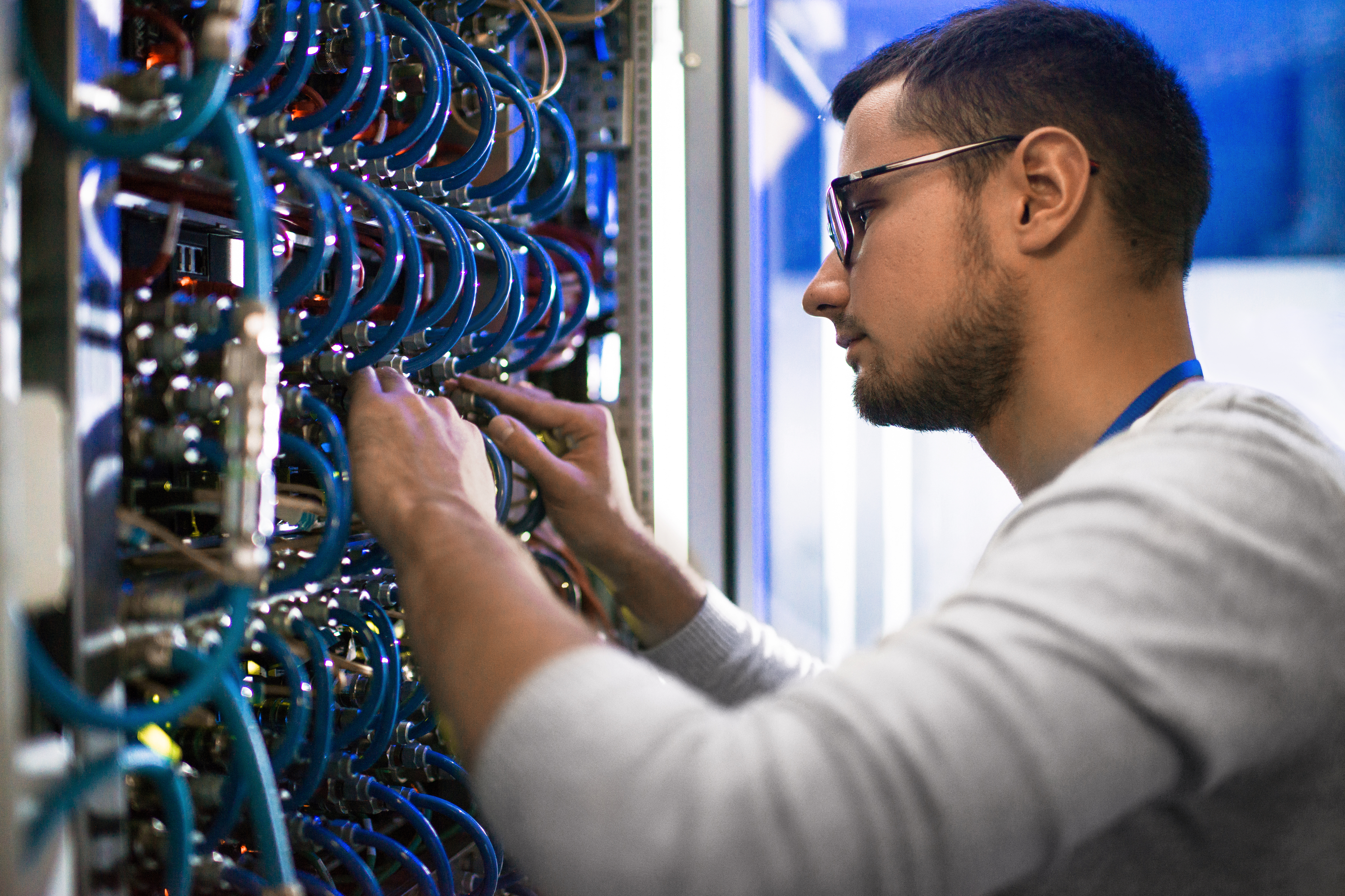 连接在服务器内阁的年轻人侧视图画象在服务器内阁在与数据中心的超级计算机一起使用时