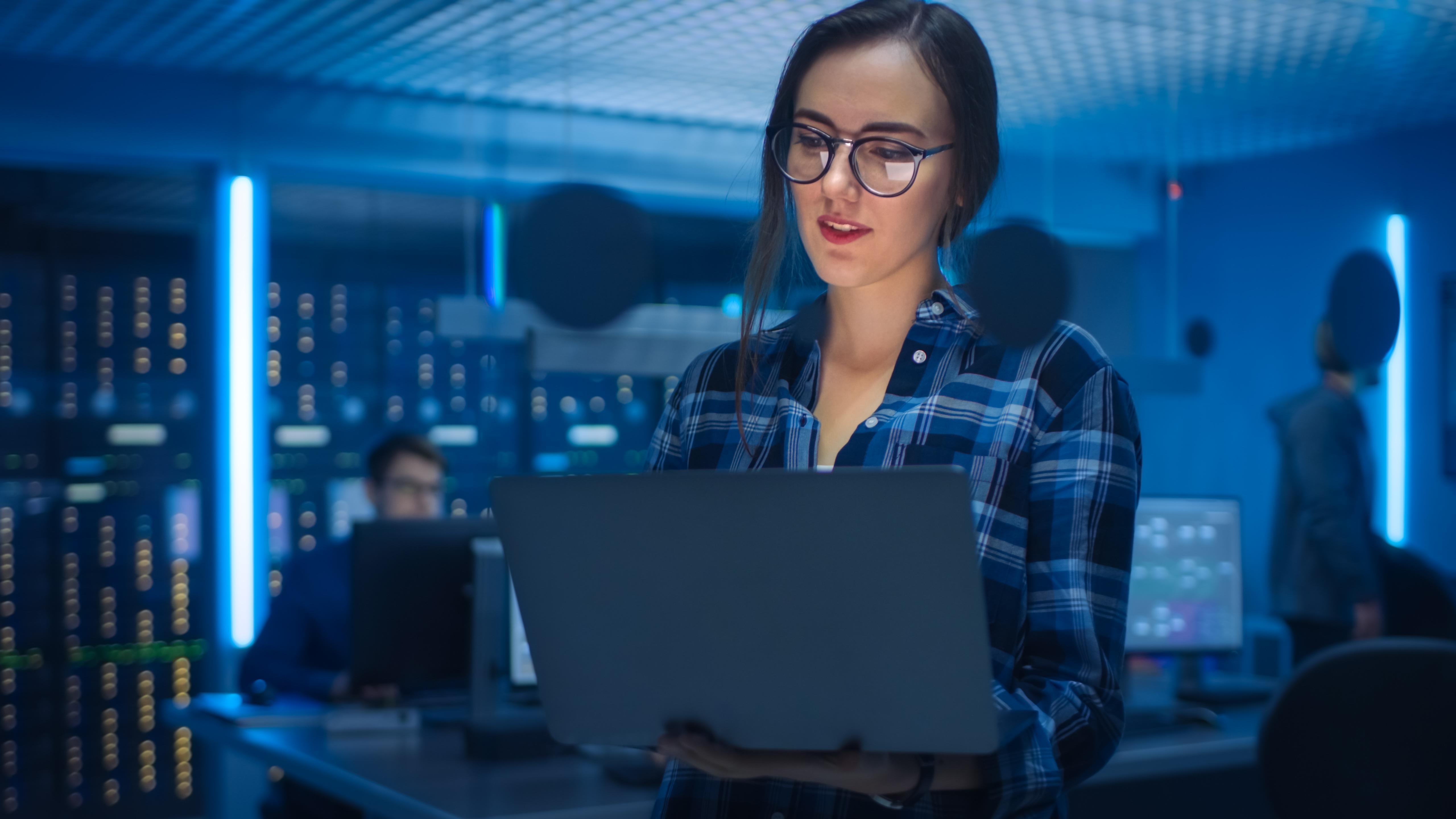 聪明的少妇佩带的玻璃的画象拿着膝上型计算机在背景技术部办公室与专家工作和功能数据服务器机架