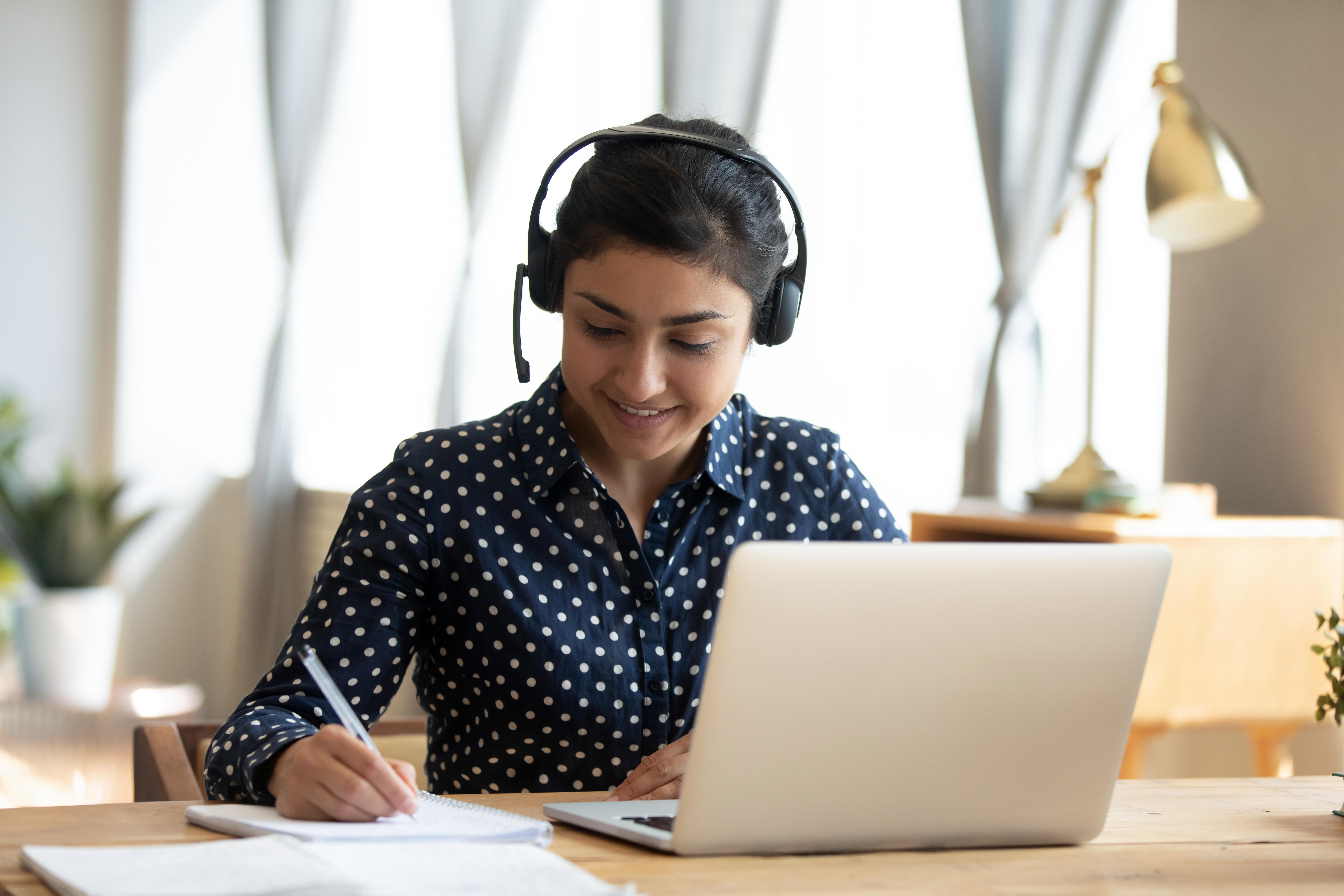 愉快的印地安女孩学生穿戴耳机在网上学习与摄象壁的老师写笔记,愉快的少妇听演讲手表网络研讨会在膝上型计算机坐,距离e学会语言教育概念