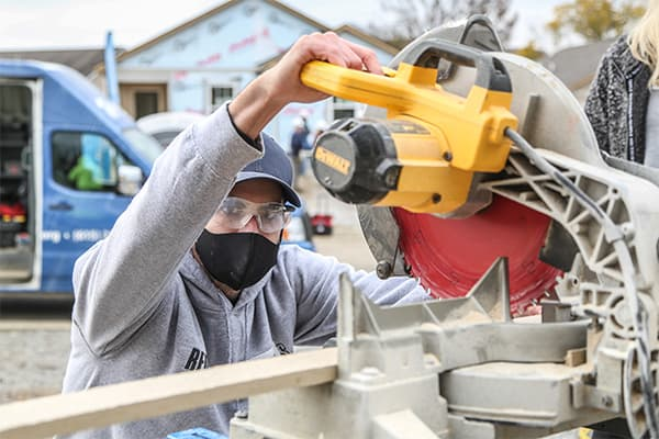 Crowe employee cutting wood and helping to build houses.