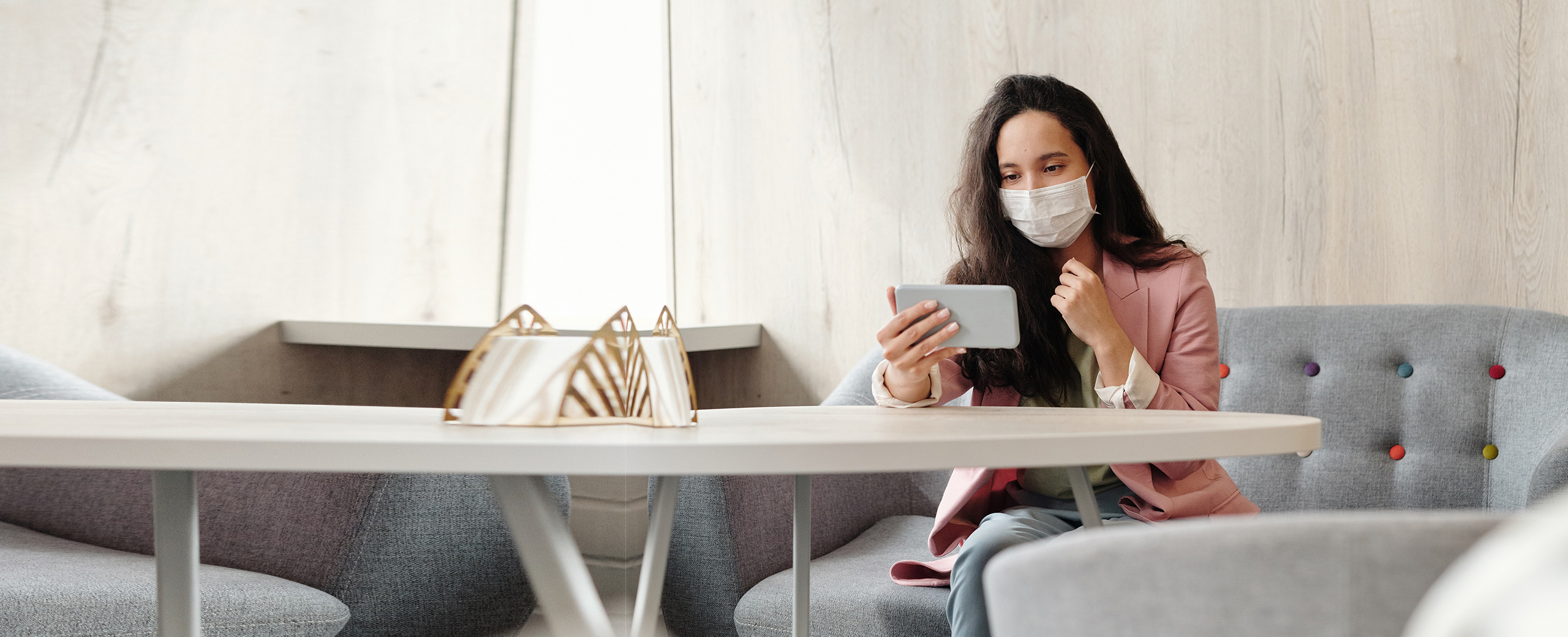 business woman in mask looking at her mobile device