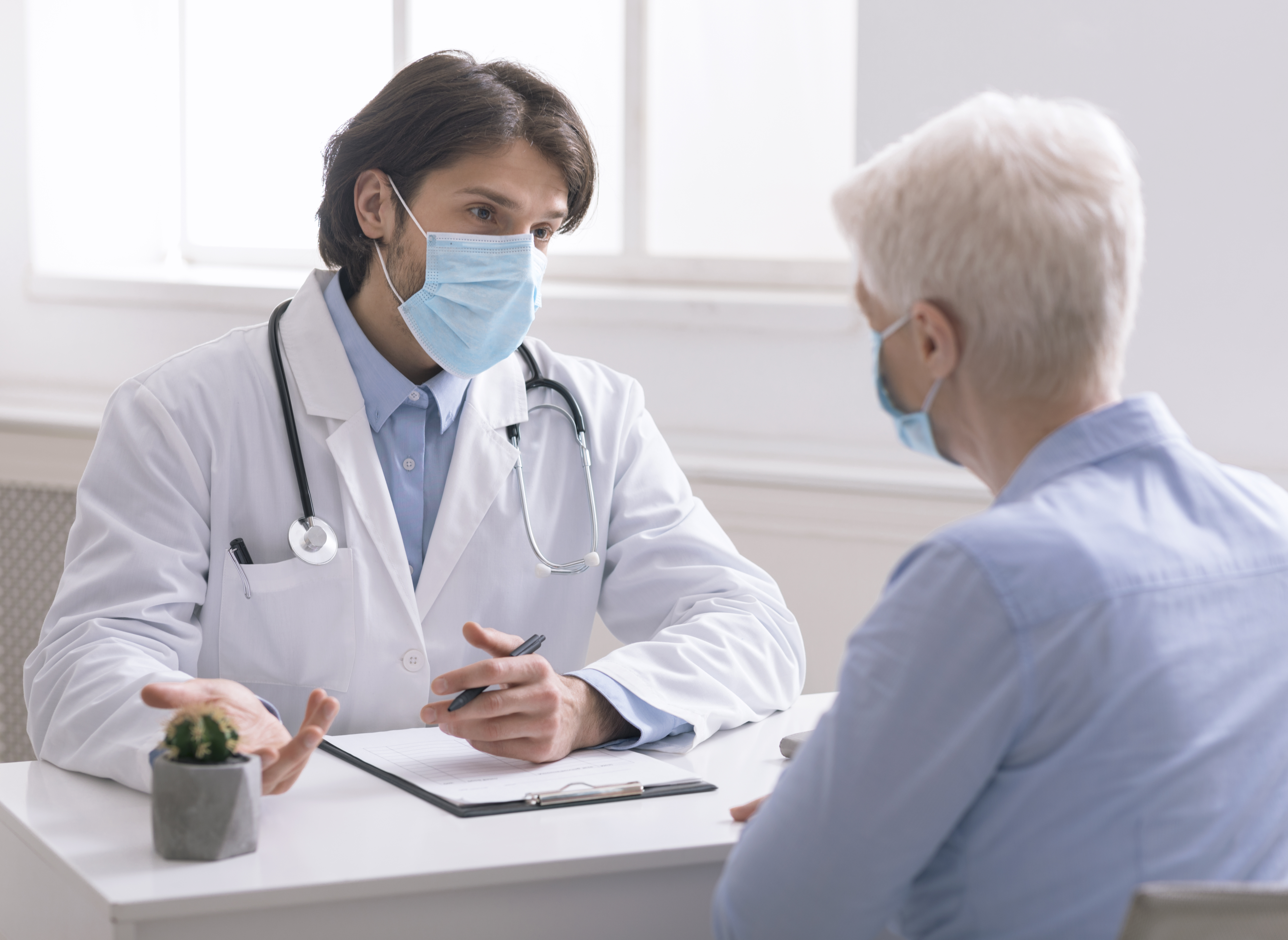 Safety medicine. Geriatrician in medical mask talking with senior patient in office