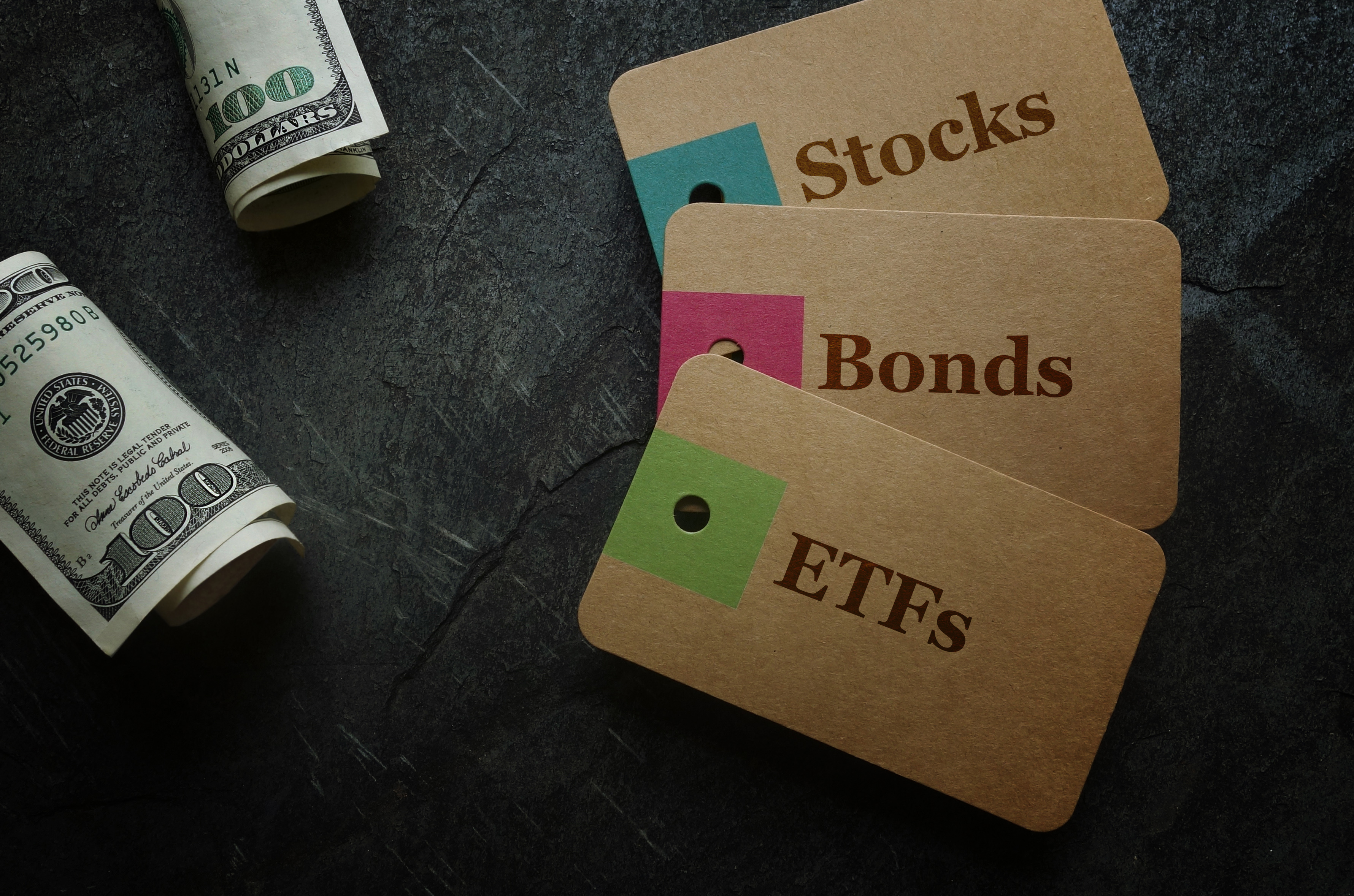 ETF (Exchange Traded Funds), Stocks and Bonds paper tags with cash on dark background