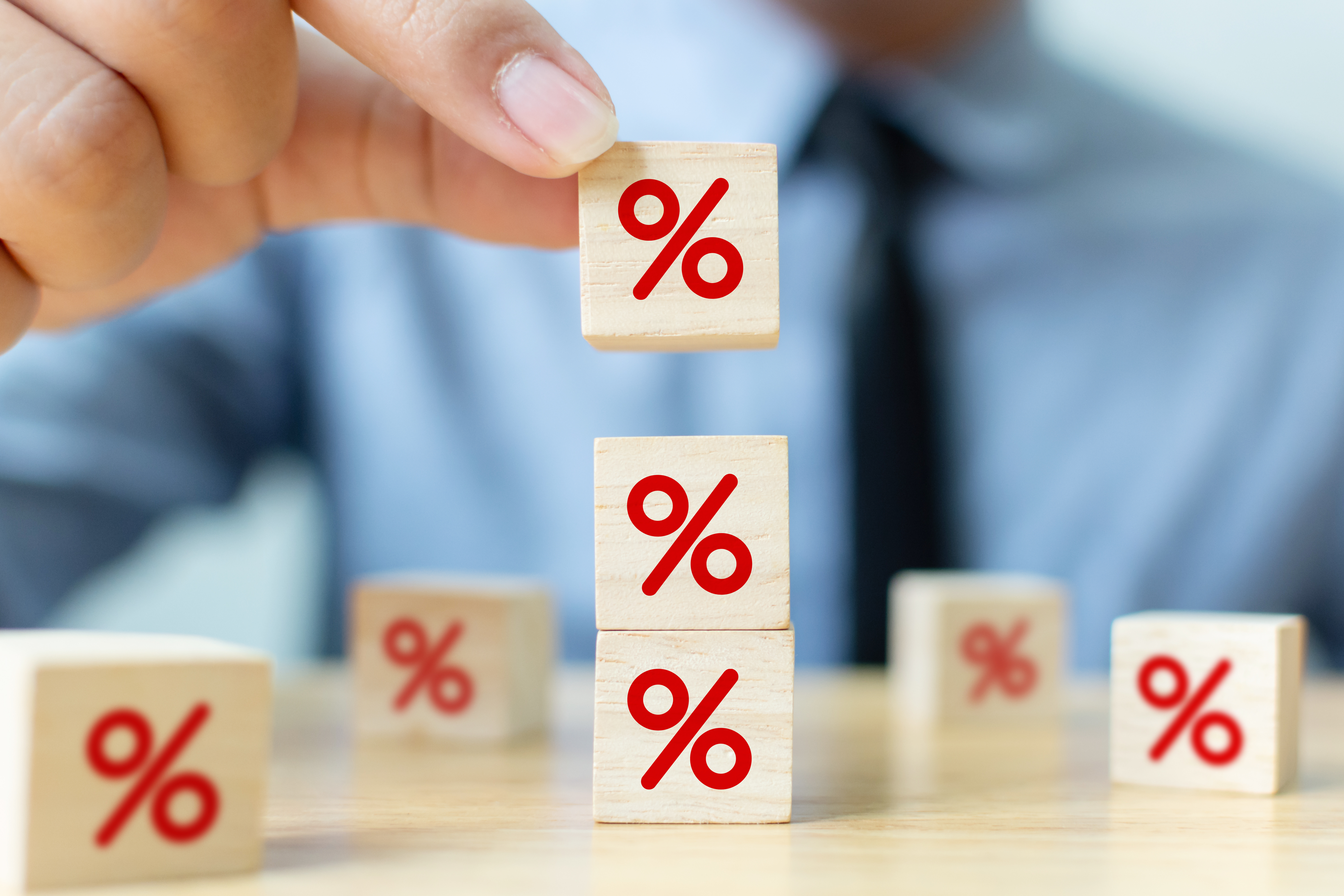 Interest rate financial and mortgage rates concept. Hand putting wood cube block increasing on top with icon percentage symbol upward direction