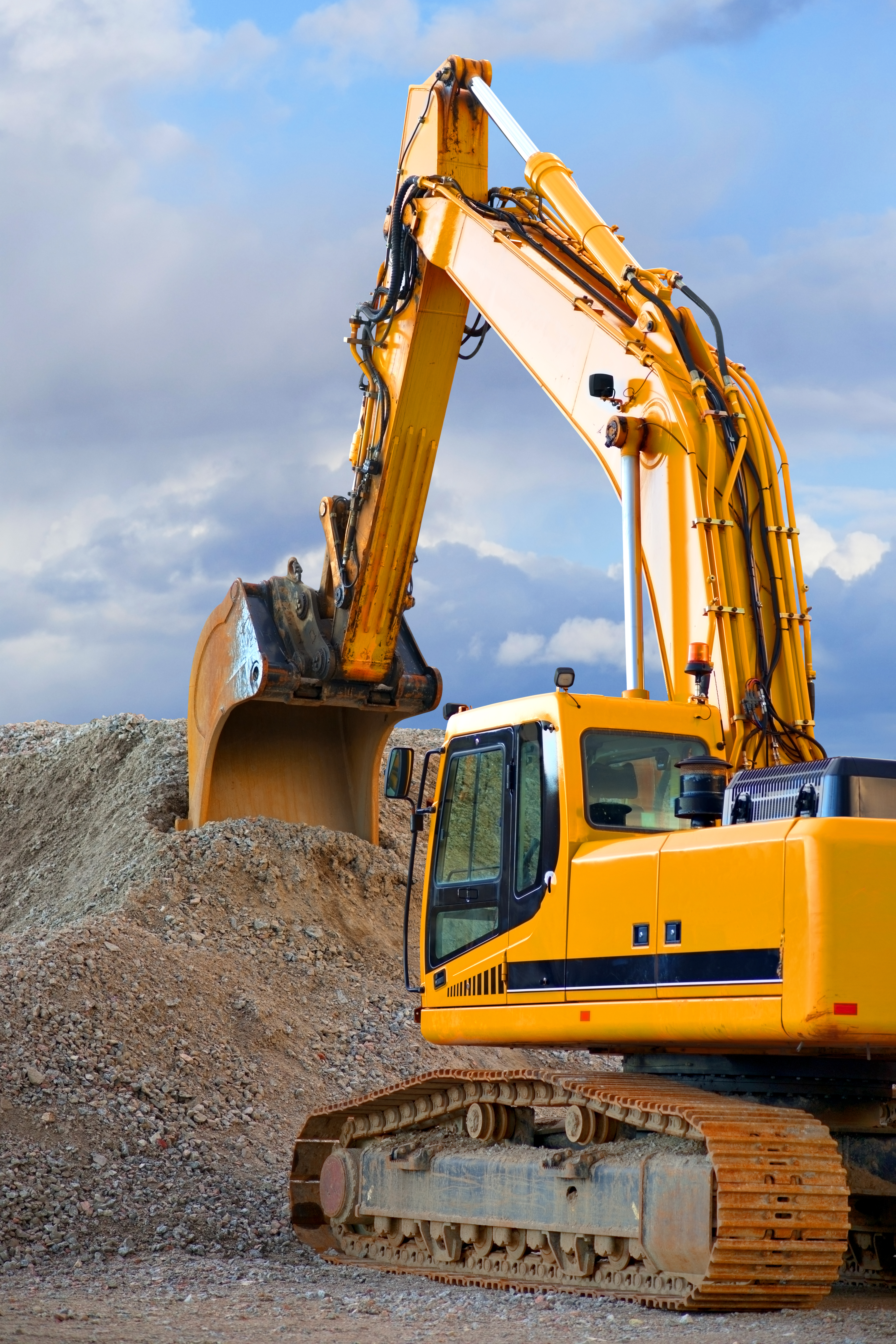 Yellow digger with big heap of gravel on blue sky