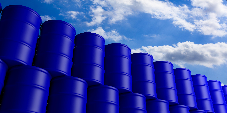 Blue oil barrels stack on blue sky background. 3d illustration