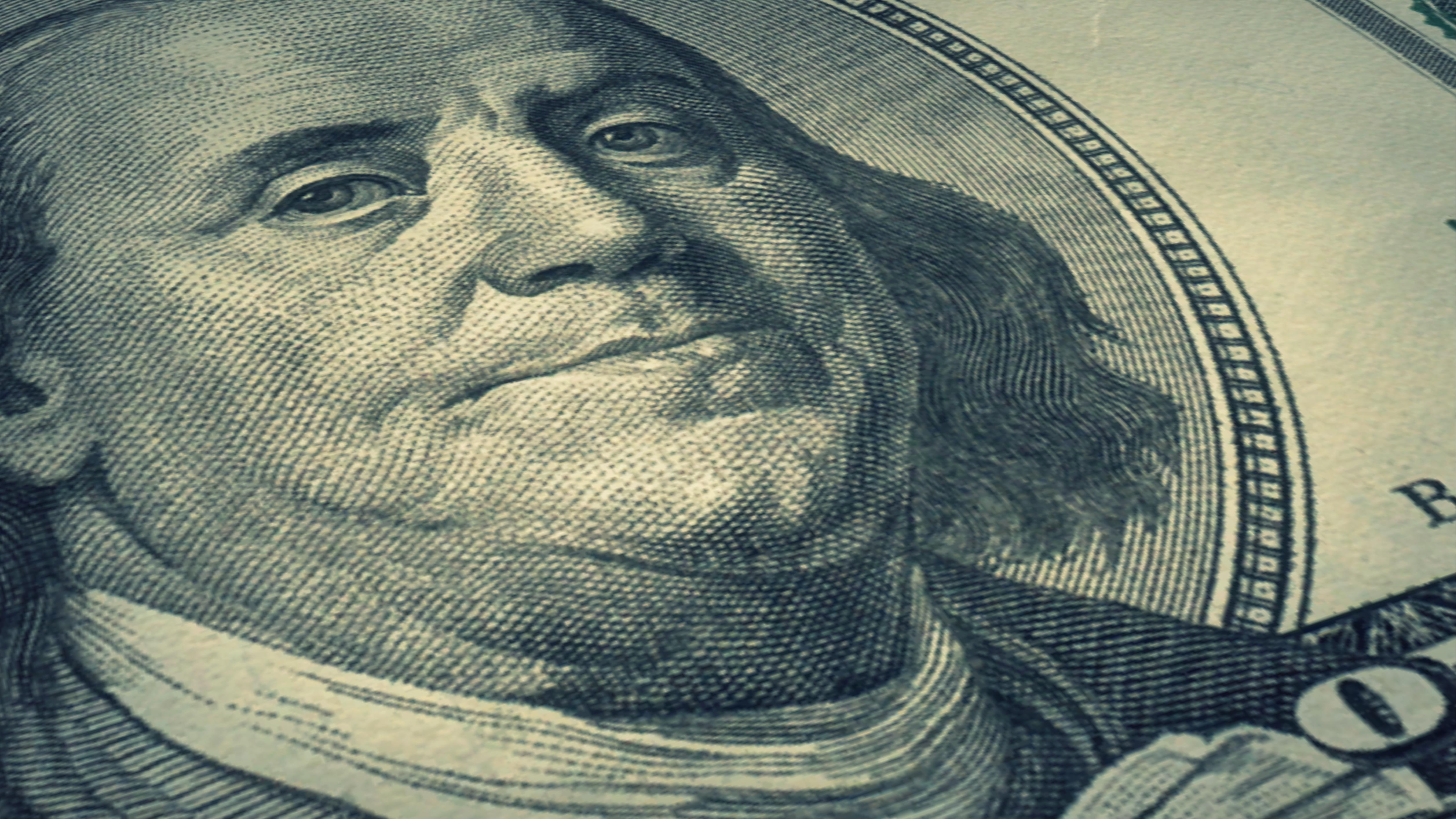 Portrait Benjamin Franklin on USA money One hundred dollars banknote pile background