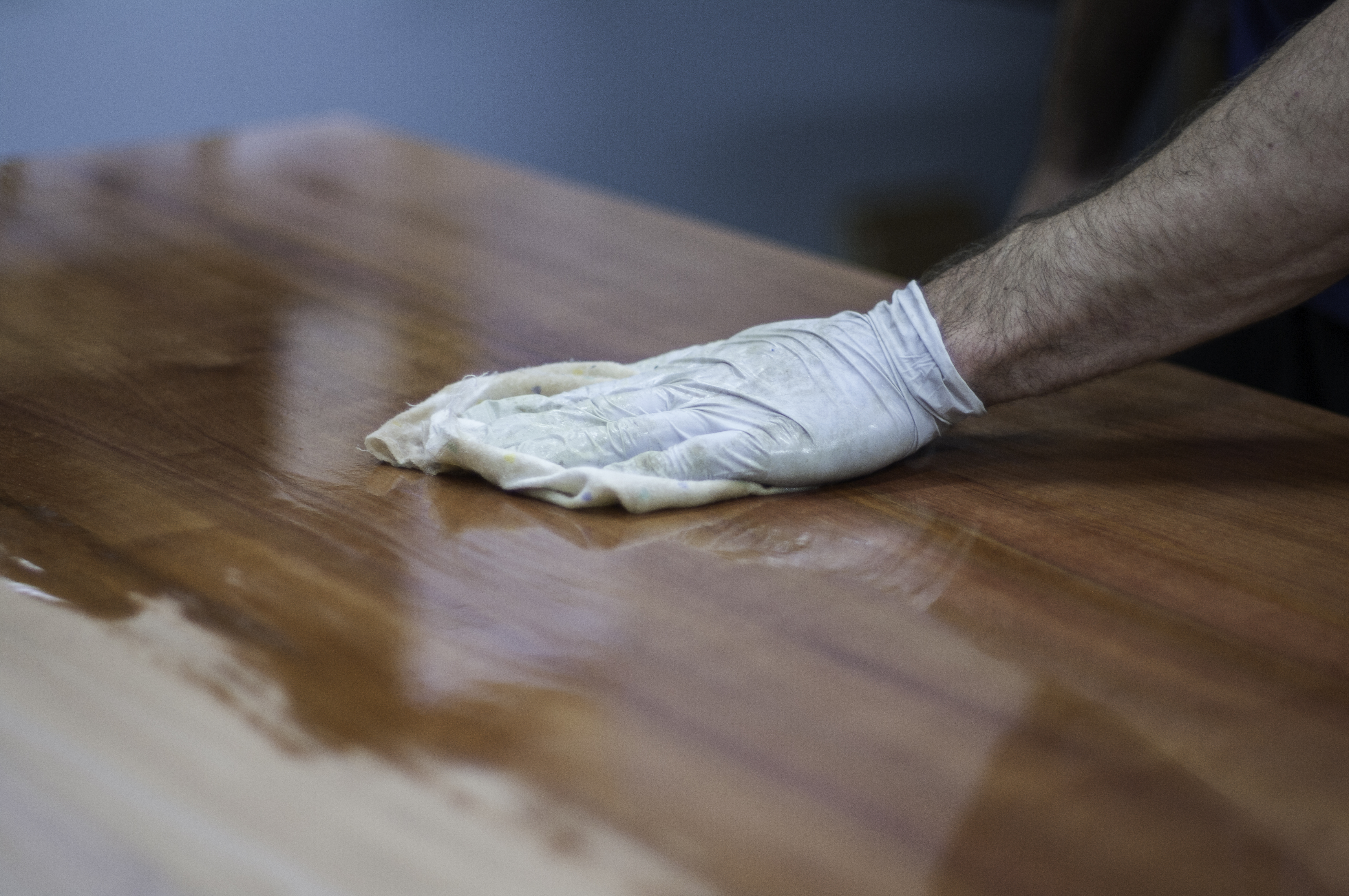 Finshing a timber table top by hand with oil or wax. French polishing wooden furniture with a rag to achieve a shiny, flawless surface. Taken in a woodworking workshop with a professional wood finisher. Fine woodwork.
