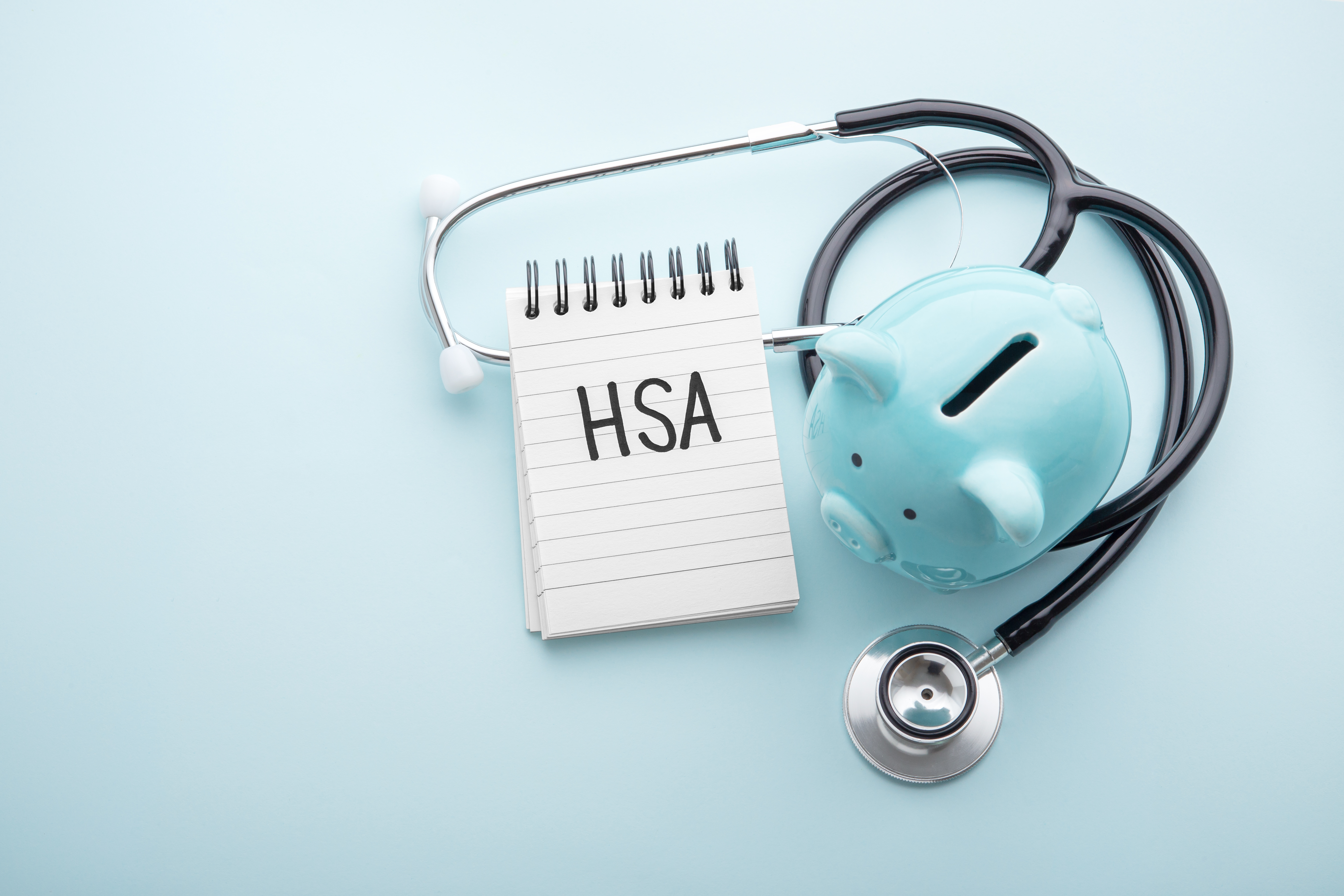 Health saving account, hsa concept, piggy bank with stethoscope on pastel blue background