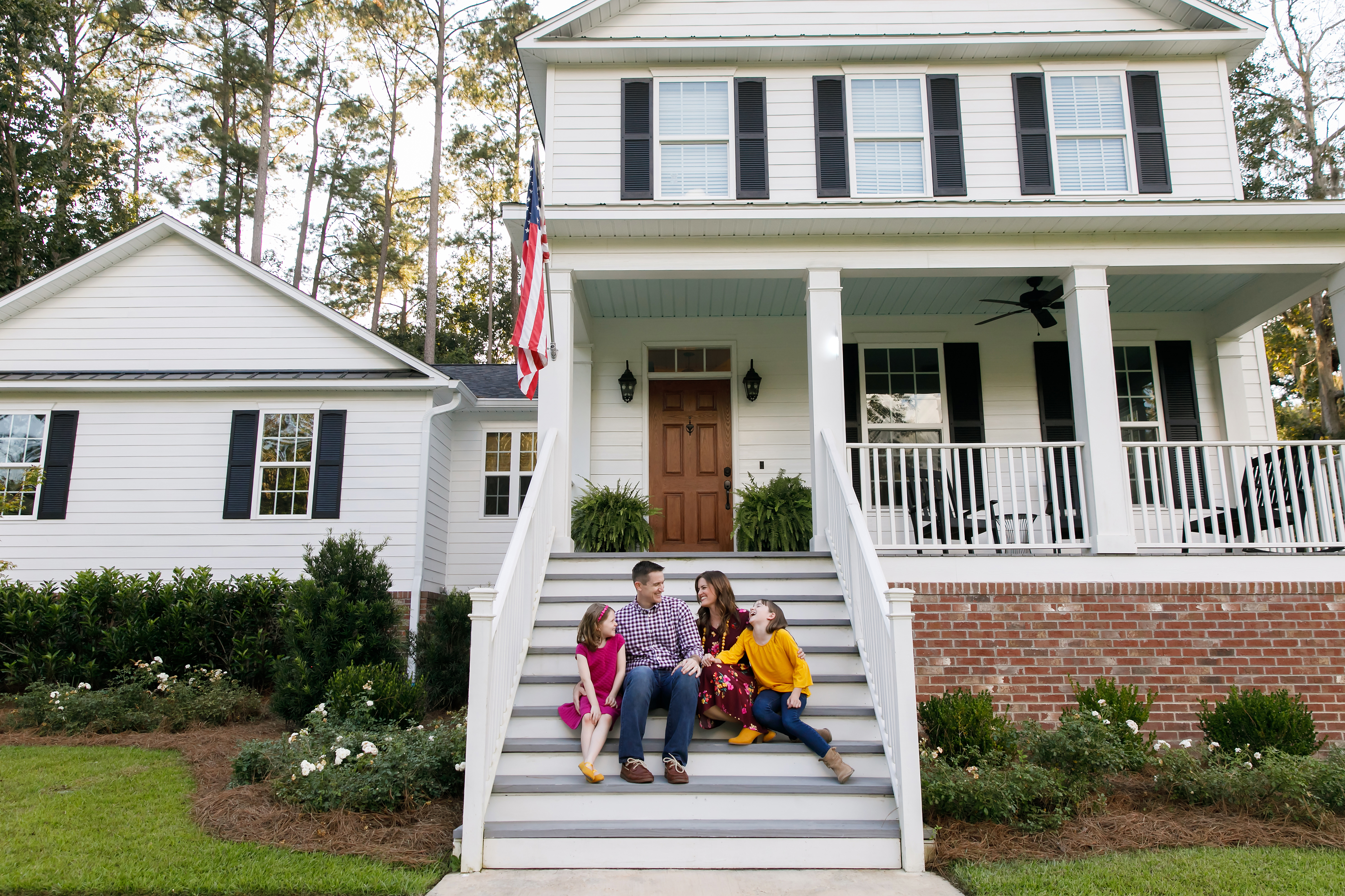 Family sitting outside on the steps of a new construction white siding farmhouse in the suburbs