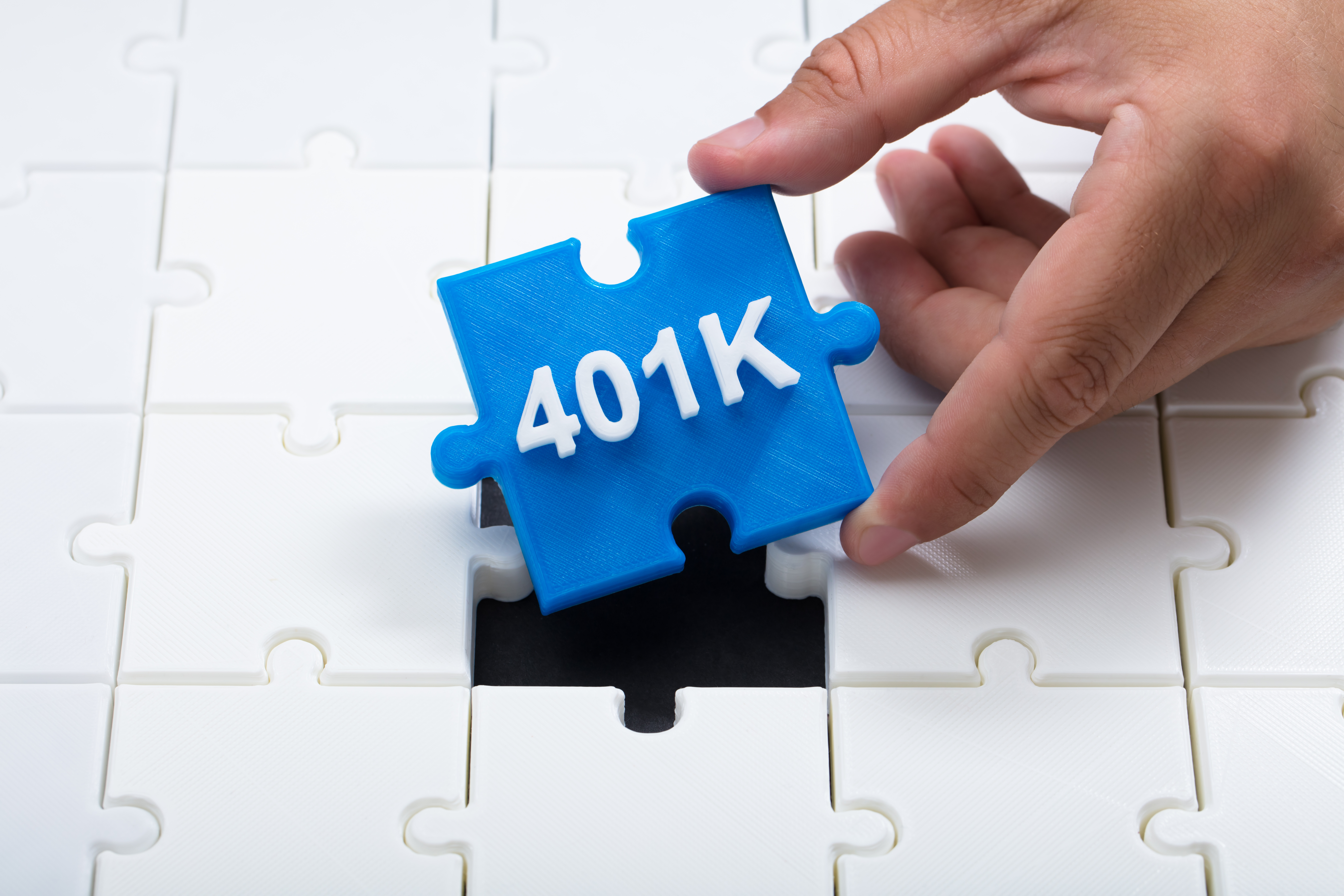 Close-up of a man's hand placing final blue 401k piece into jigsaw puzzle