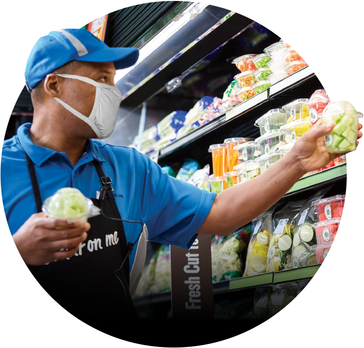 Masked store associate stocking fresh produce items