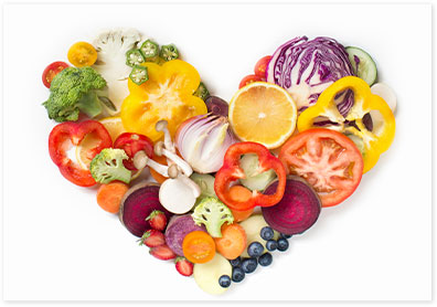 Heart composed of fresh cut vegetables on white background