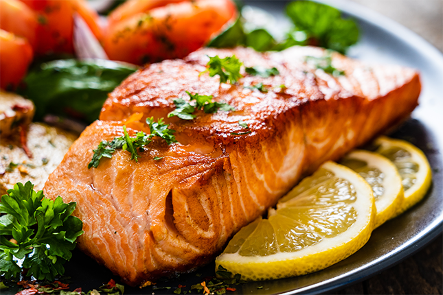 Fresh Cooked Salmon filet with lemon slices and vegetables