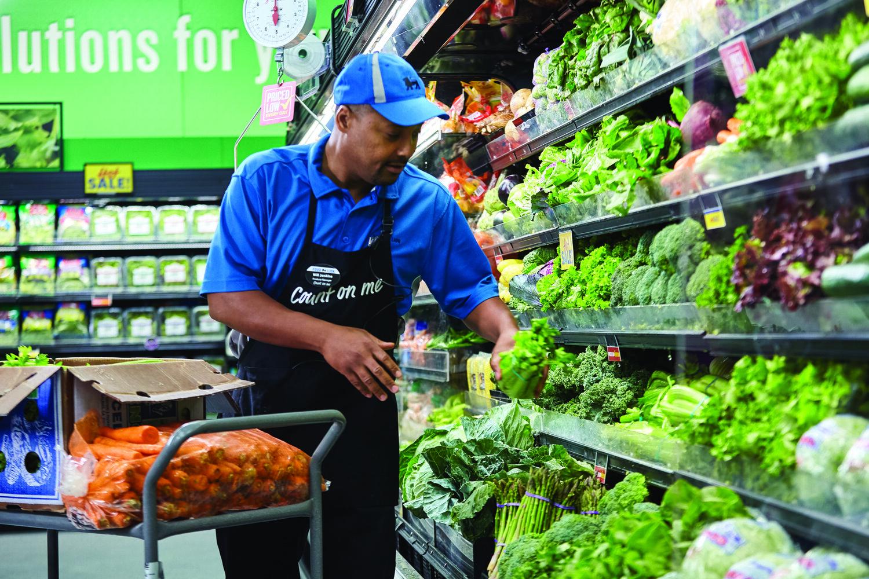 Greg Finchum grabbing fresh herbs from the produce shelf