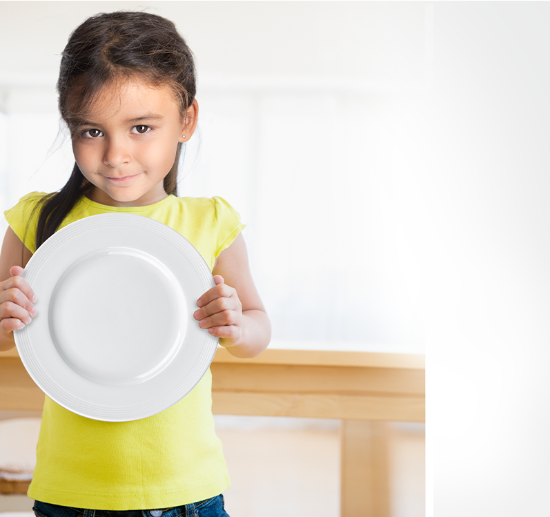 Young girl with a yellow shirts holding a empty dinner plate.
