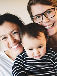 Smiling female couple with their infant child
