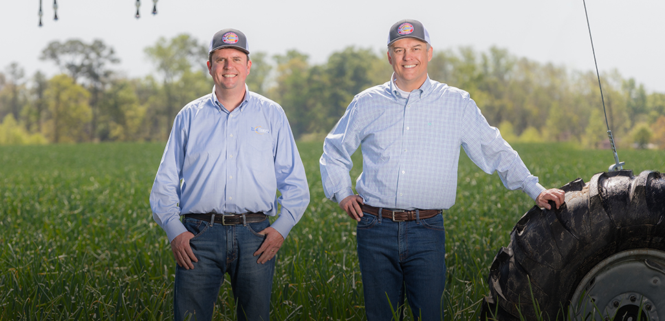 John & Mark Shuman standing in one of their fields, leaning on a tractor tire