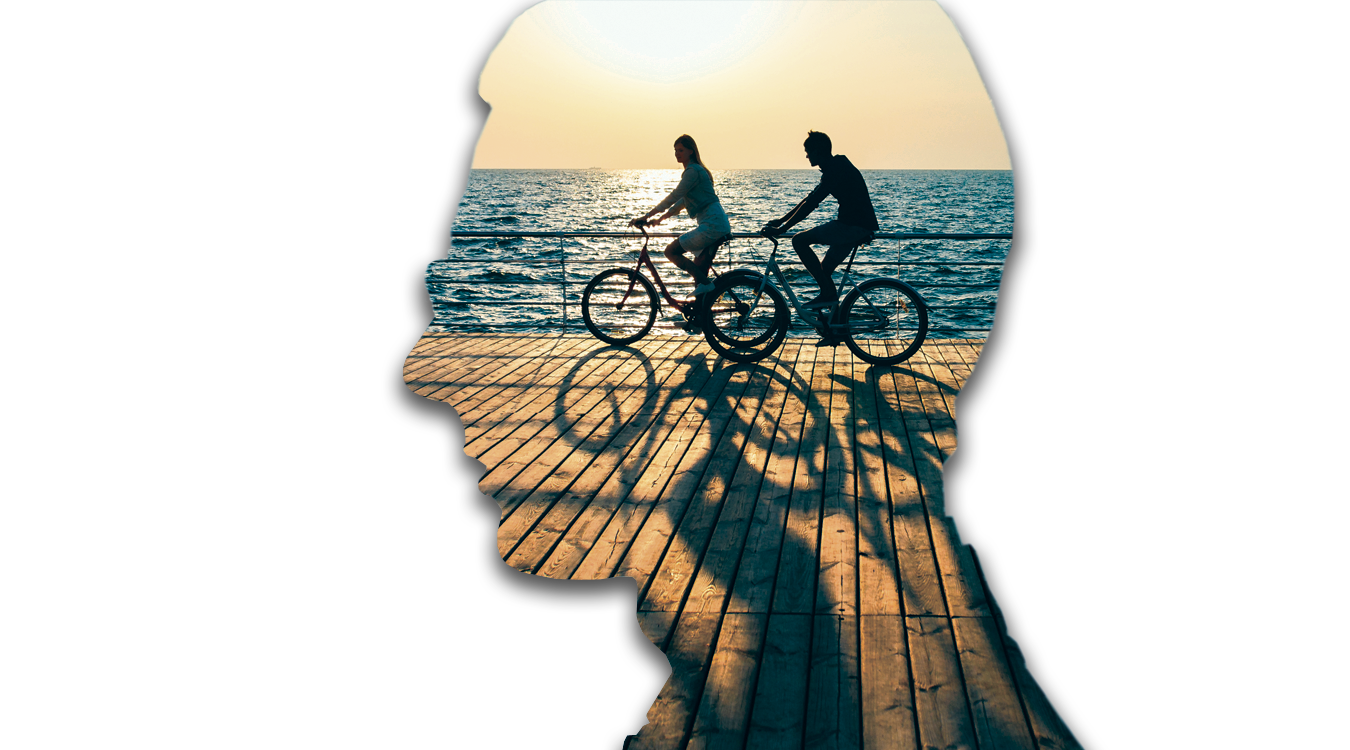 Image of two bikers riding their bikes on a pier by the water, inside a head shaped outline