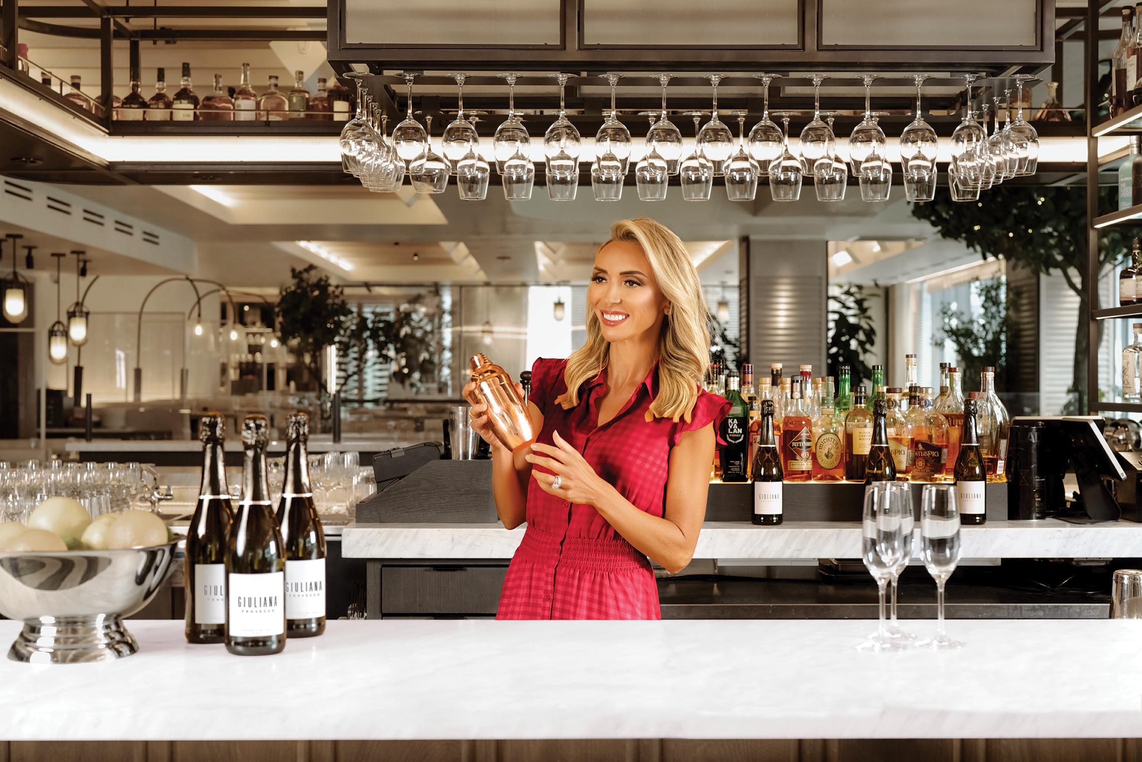 Giuliana Rancic standing behind a bar mixing a drink.
