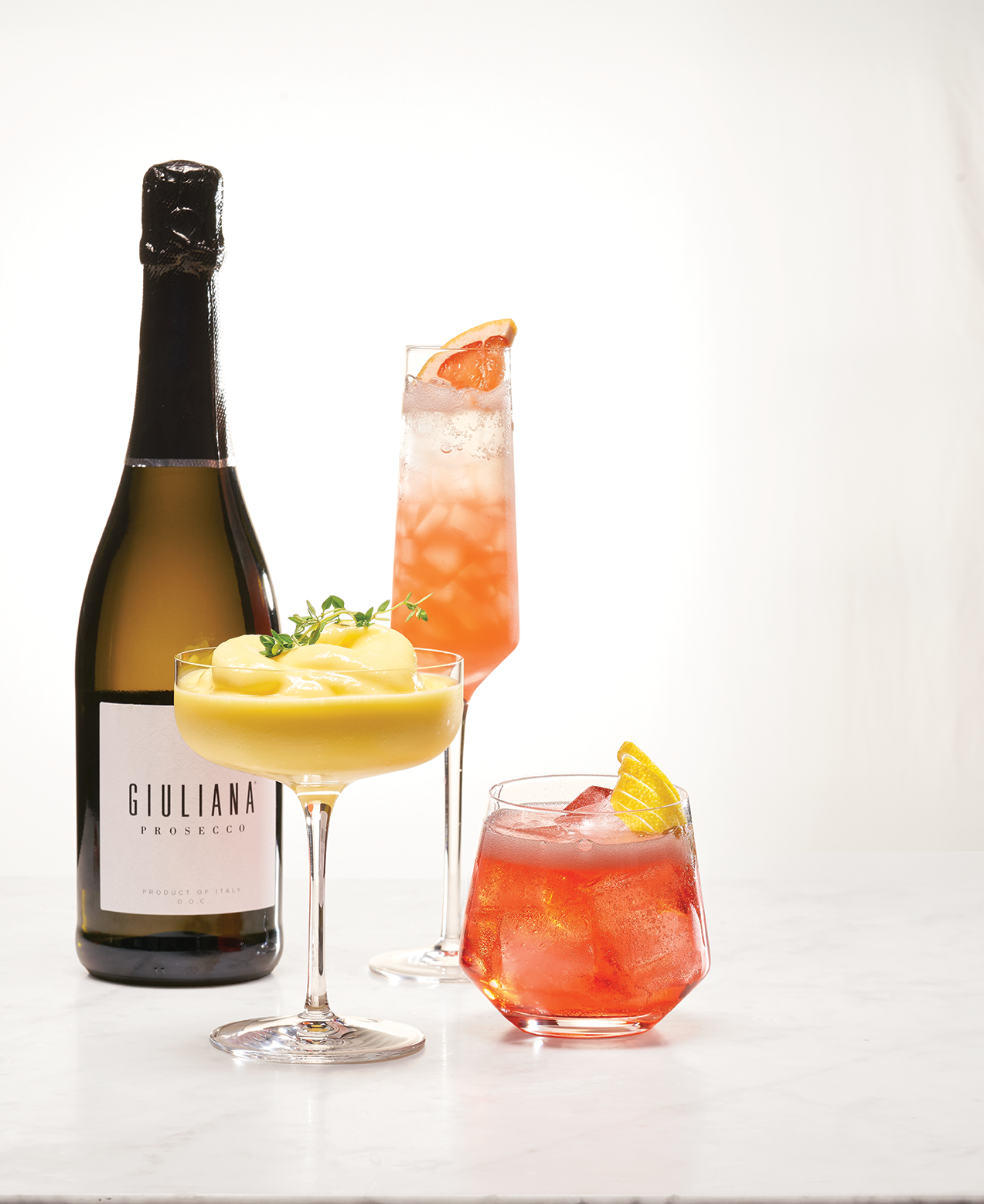 A display of the three cocktail recipes and a bottle of Giuliana Prosecco.