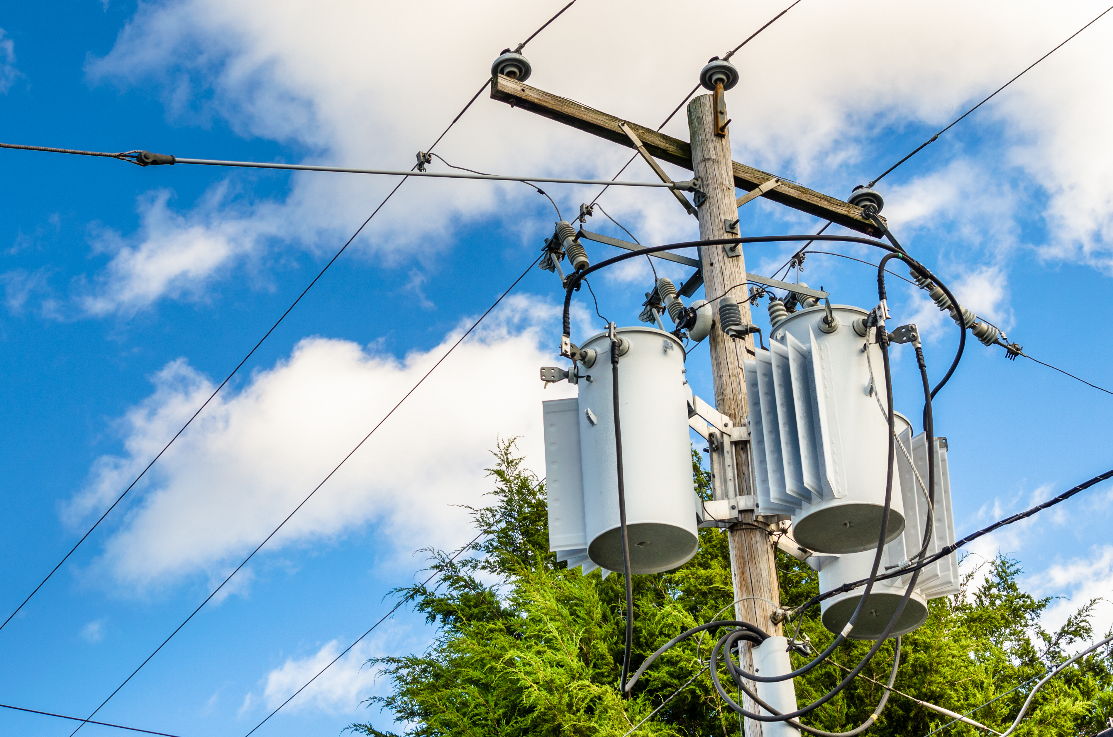 Photo of Electricity Distribution Pole with Transformers aginst Bleu Sky with Clouds