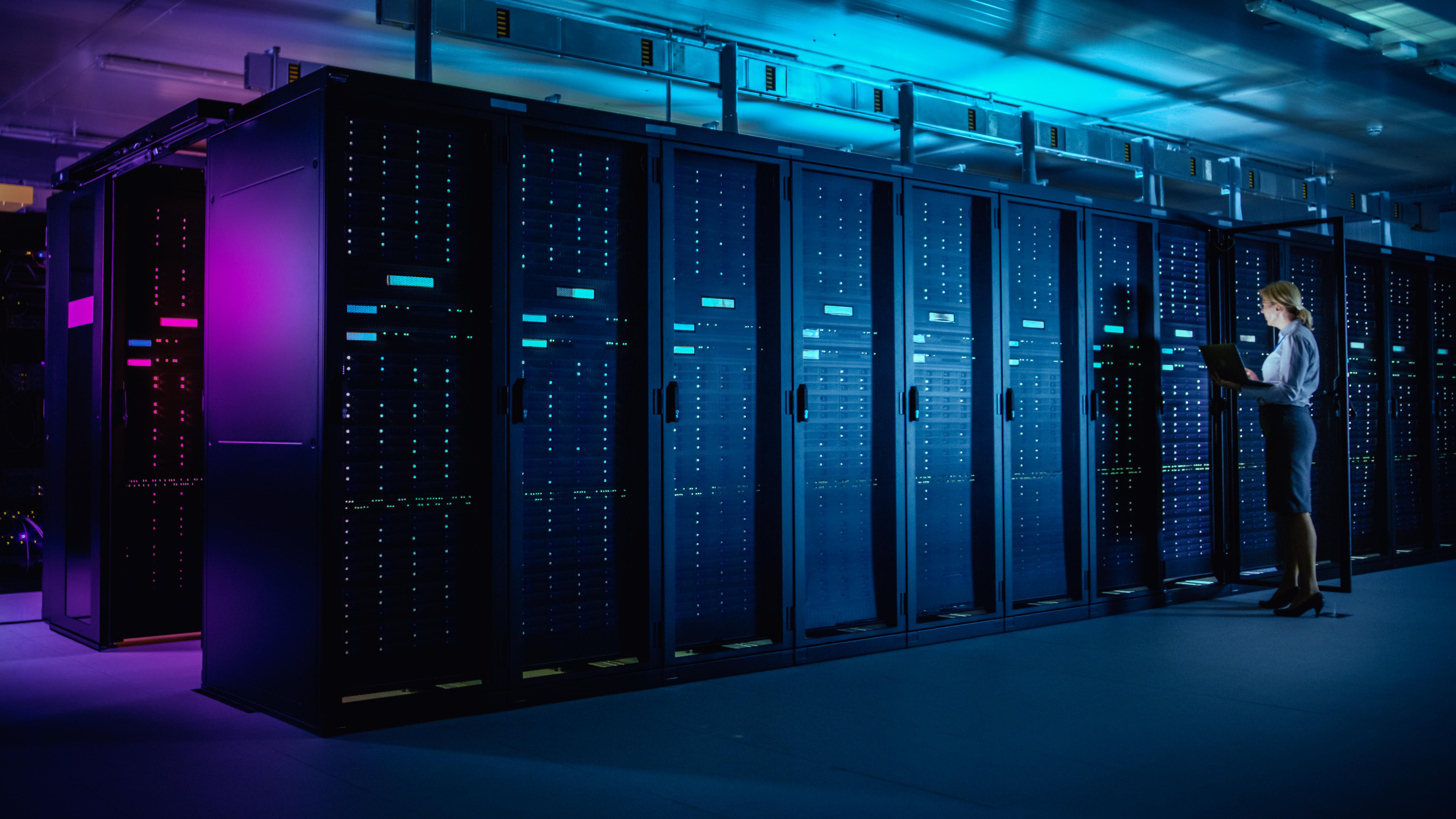 In Data Center: IT Technician Running Maintenance Programme on Laptop, Controls Operational Server Rack Optimal Functioning. Modern High-Tech Telecommunications Operational Data Center in Neon Lights.