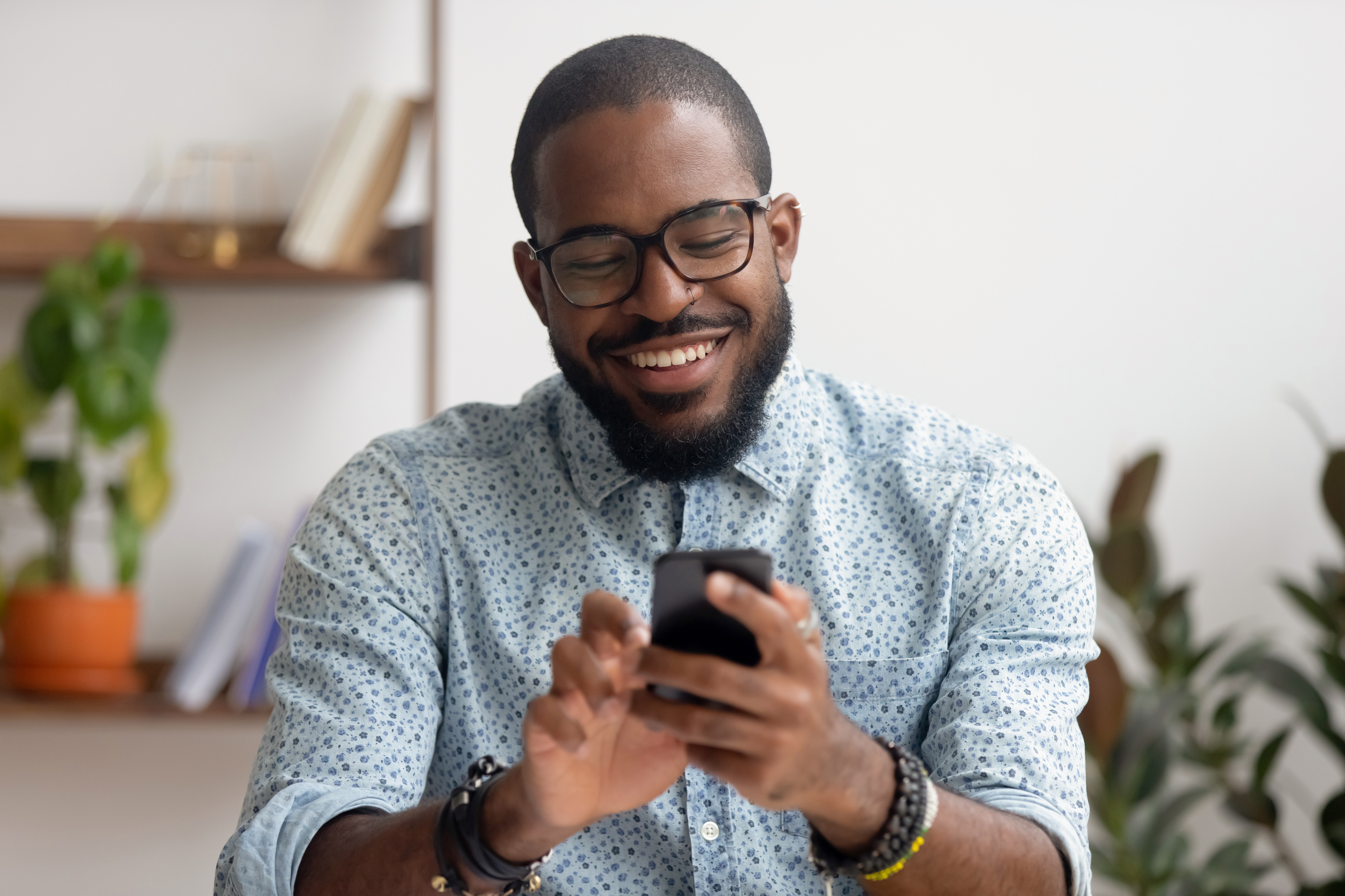 Happy african american businessman using phone mobile corporate apps at workplace texting sms, smiling black man looking at smartphone browsing internet, office technology and digital communication