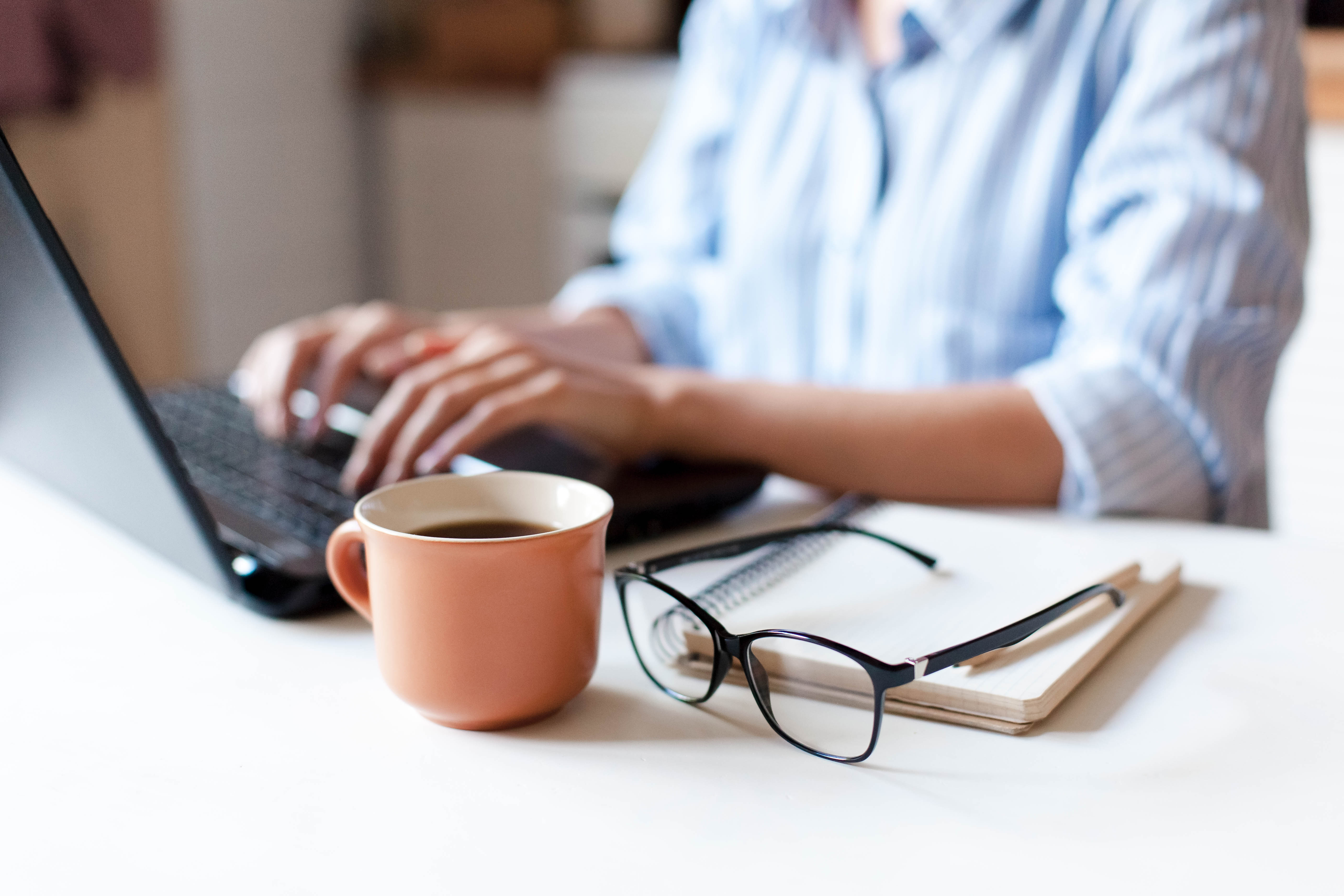 Remote working from home. Freelancer workplace in kitchen with laptop, cup of coffee, spectacles. Concept of distance learning, isolation, female business, shopping online. Close up of woman hands.