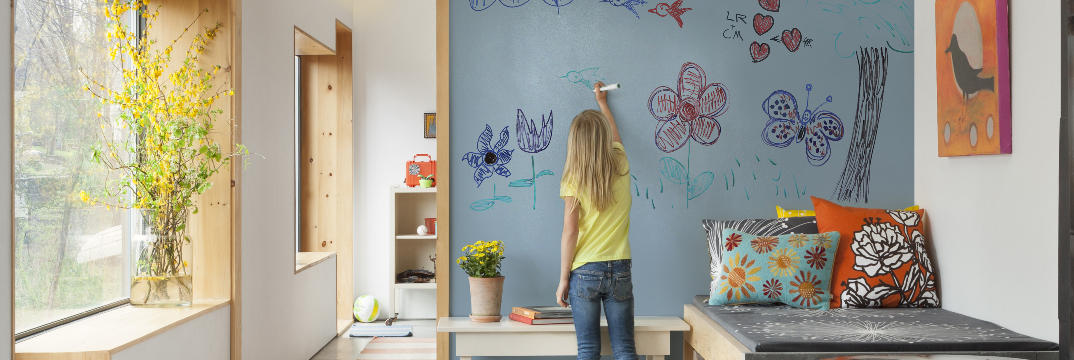 Female child drawing colorful, fun sketches on her dry-erase wall in office room