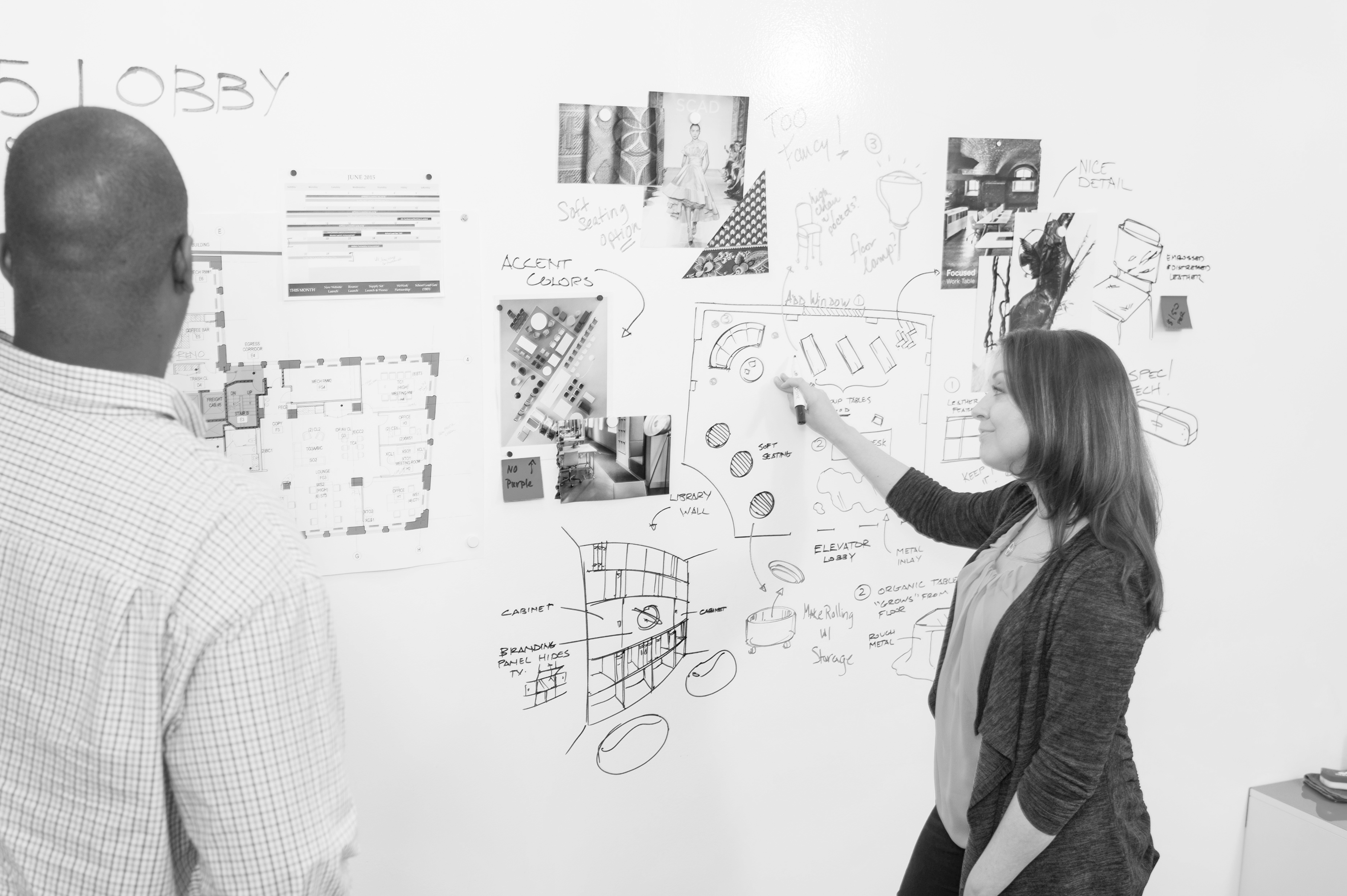 Woman and man brainstorming with sketches on office walls