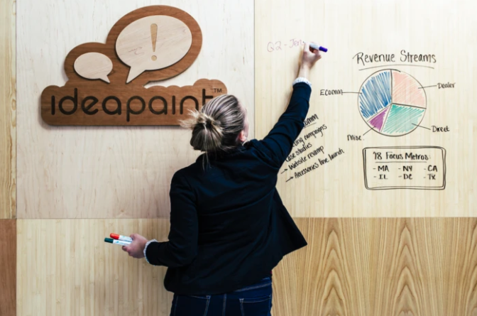 Woman writing notes on wooden wall in office setting using IdeaPaint Clear